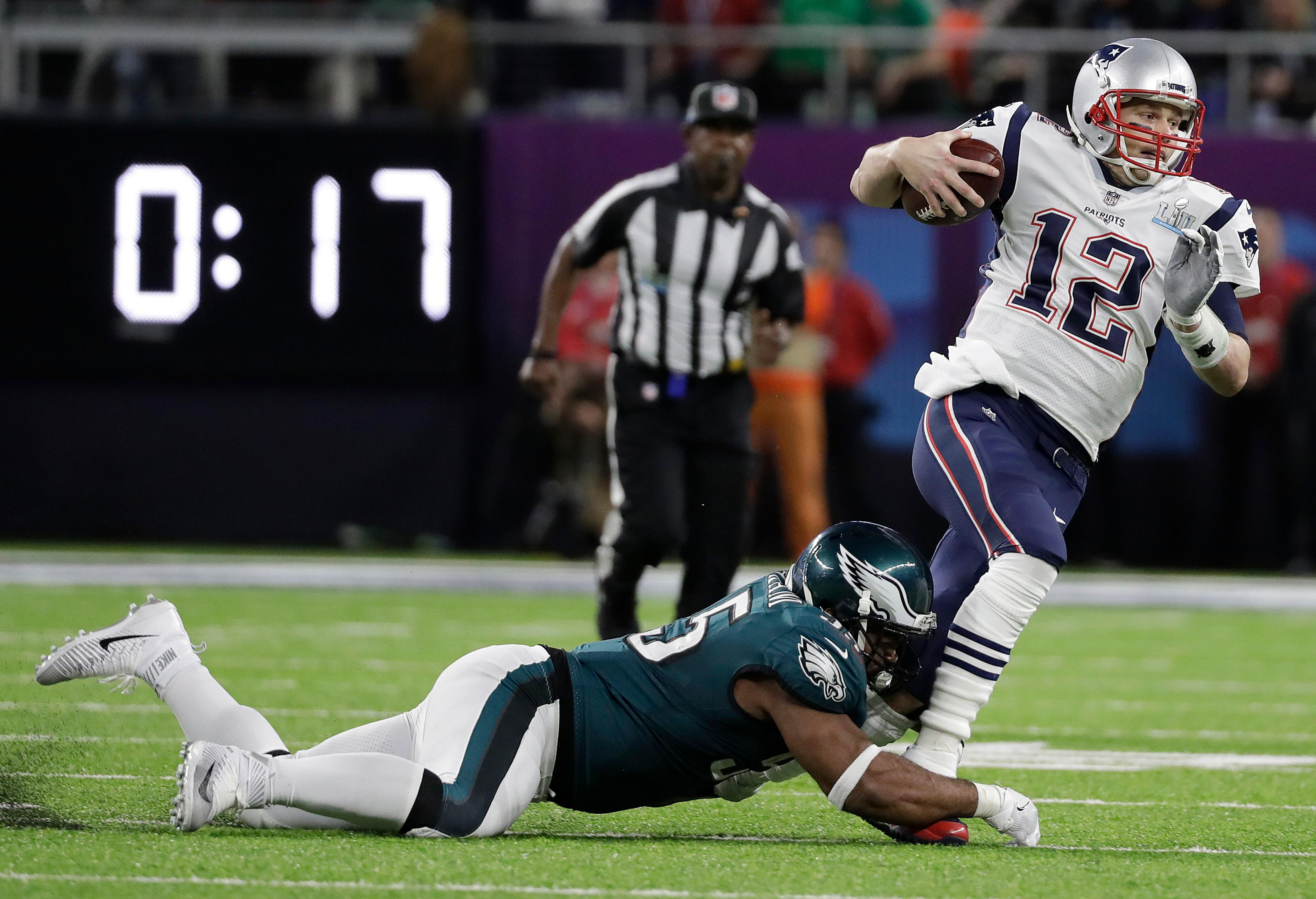 New England Patriots' Tom Brady (12) runs from Philadelphia Eagles' Brandon Graham during the first half of the NFL Super Bowl 52 football game Sunday, Feb. 4, 2018, in Minneapolis. (AP Photo/Mark Humphrey)