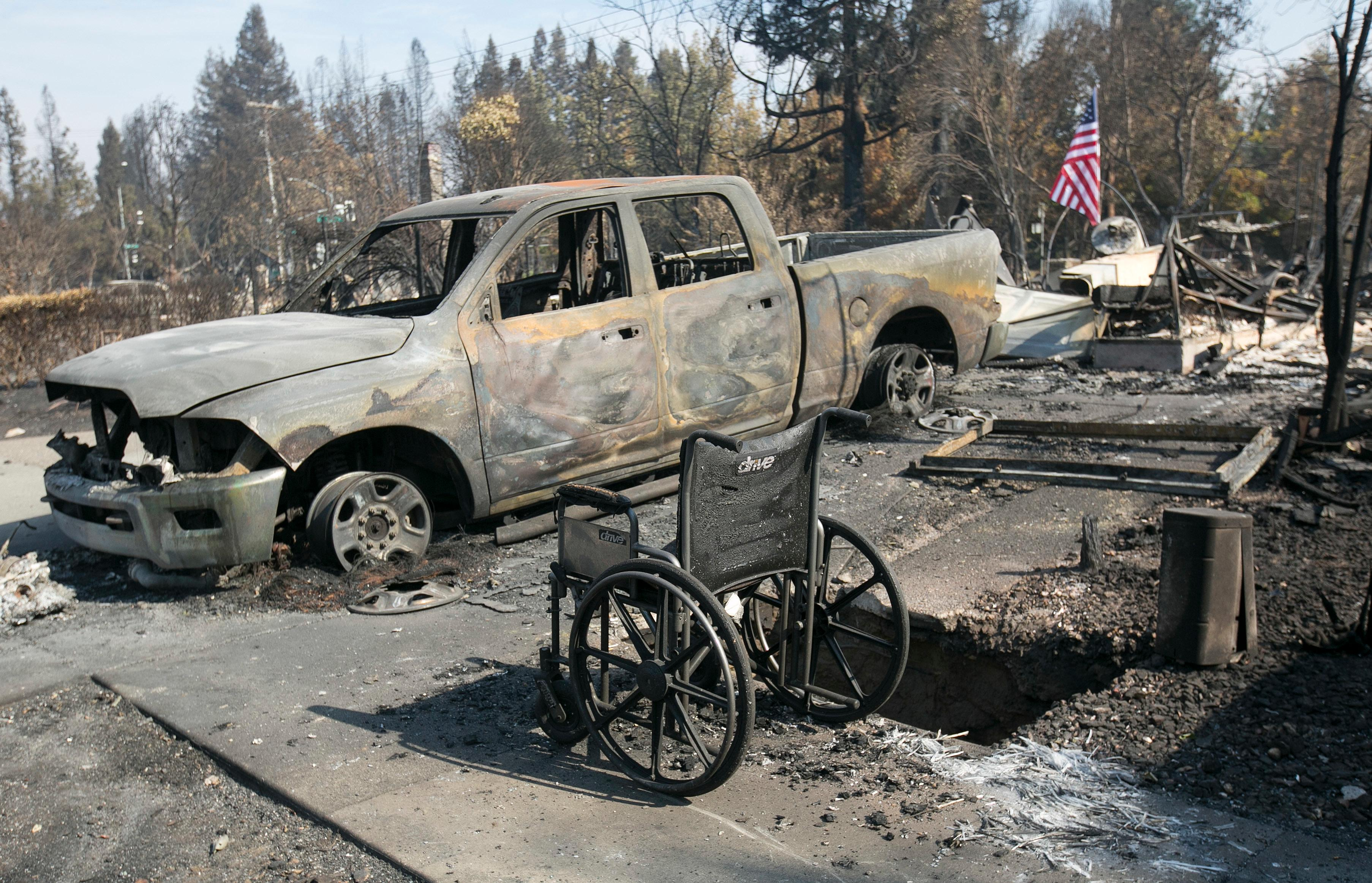 A scorched truck and wheelchair sit outside the charred remains of a house in the Coffey Park area of Santa Rosa, Calif., Monday, Oct. 16, 2017. (AP Photo/Rich Pedroncelli)