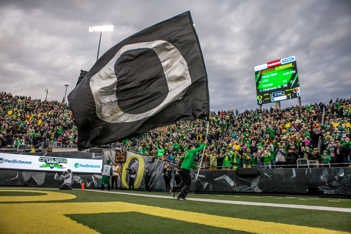 An Oregon cheerleader runs an Oregon flag up the field before the game. The Oregon Ducks lead the Oregon State Beavers 52 to 7 at the end of the first half of the 121st Civil War game on Saturday, November 25, 2017 at Autzen Stadium in Eugene, Ore. Photo by Ben Lonergan, Oregon News Lab