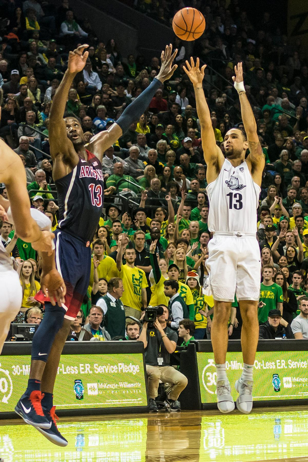 Oregon's Paul White (13) shoots for three over Arizona's DeAdre Ayton (13) in their matchup at Matthew Knight Arena Saturday. The Ducks upset the fourteenth ranked Wildcats 98-93 in a stunning overtime win in front of a packed house of over 12,000 fans for their final home game to improve to a 19-10 (9-7 PAC-12) record on the season. Oregon will finish out regular season play on the road in Washington next week against Washington State on Thursday, then Washington on the following Saturday. (Photo by Colin Houck)