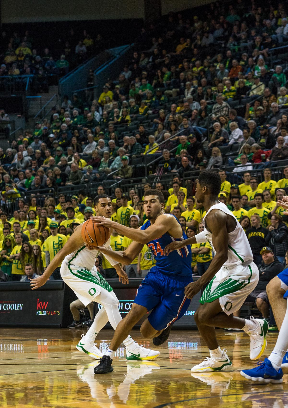 Boise State Bronco Alex Hobbes (#34) attempts to break through the University of Oregon's Victor Bailey Jr. (#10) and Keith Smith (#11). The Boise State Broncos defeated the University of Oregon Ducks 73 – 70 at Matthew Knight Arena in Eugene, Ore., on December 1, 2017. Photo by Kit MacAvoy, Oregon News Lab
