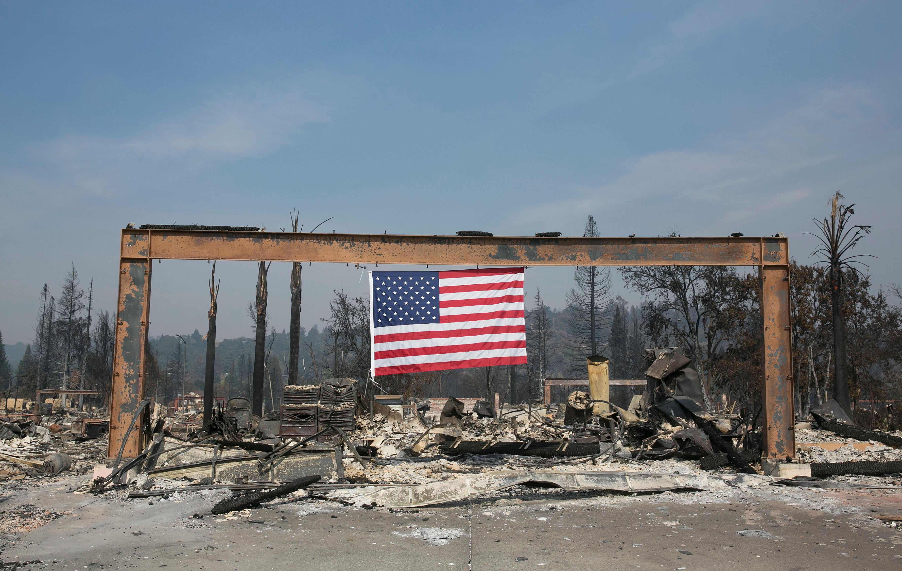 A United States flag hangs from the charred remains of a home in Santa Rosa, Calif. Monday, Oct. 16, 2017. Massive wildfires swept through area last week destroying thousands of homes and businesses and claiming the lives of dozens of people who were unable to escape the flames. (AP Photo/Rich Pedroncelli)