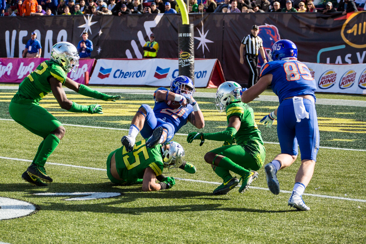 Boise State running back Ryan Wolpin (#21) falls over an Oregon defender. The Oregon Ducks trail the Boise State Broncos 14 to 24 at the end of the first half of the Las Vegas Bowl at Sam Boyd Stadium in Las Vegas, Nevada. Photo by Ben Lonergan, Oregon News Lab