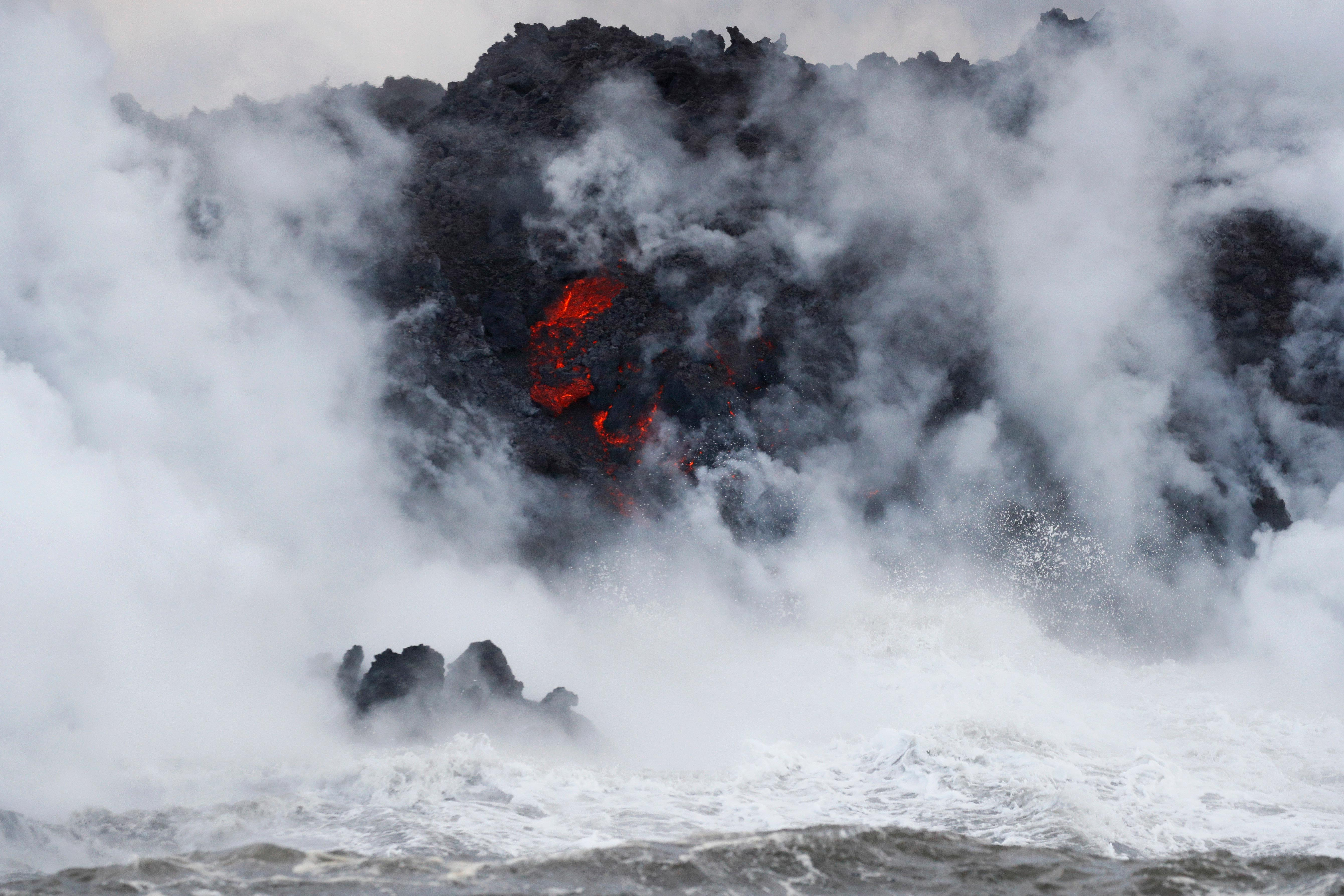 FILE - This May 20, 2018 file photo shows steam rising as lava flows into the ocean near Pahoa, Hawaii. White plumes of acid and extremely fine shards of glass billowed into the sky over Hawaii as molten rock from Kilauea volcano poured into the ocean, creating yet another hazard from an eruption that began more than two weeks ago: A toxic steam cloud. (AP Photo/Jae C. Hong, file)