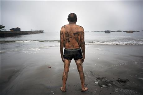 Teodocio Perez, 71, covered with a thin layer of wet sand, looks out at the Pacific Ocean during his morning exercises on the Playa de Pescadores shore in Lima, Peru, Wednesday, April 2, 2014.