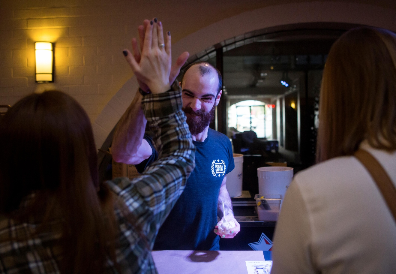 Jay Hain of Full Tilt Ice Cream high-fives a customer before handing over the Bourbon Special, an ice cream made with brown sugar bourbon, bacon, and salted caramel, at the Bourbon & Bacon Fest in SODO. (Sy Bean / Seattle Refined)