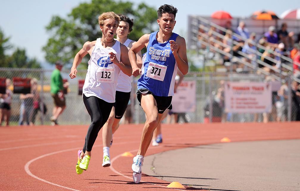 Andy Atkinson / Mail TribuneSouth Medford's Luke Ramirez (371) fights off Grants Pass's Daniel Beckstead (132) heading into the final lap to win the 1,500-meter run at the SWC Championships meet at North Medford High School Saturday.
