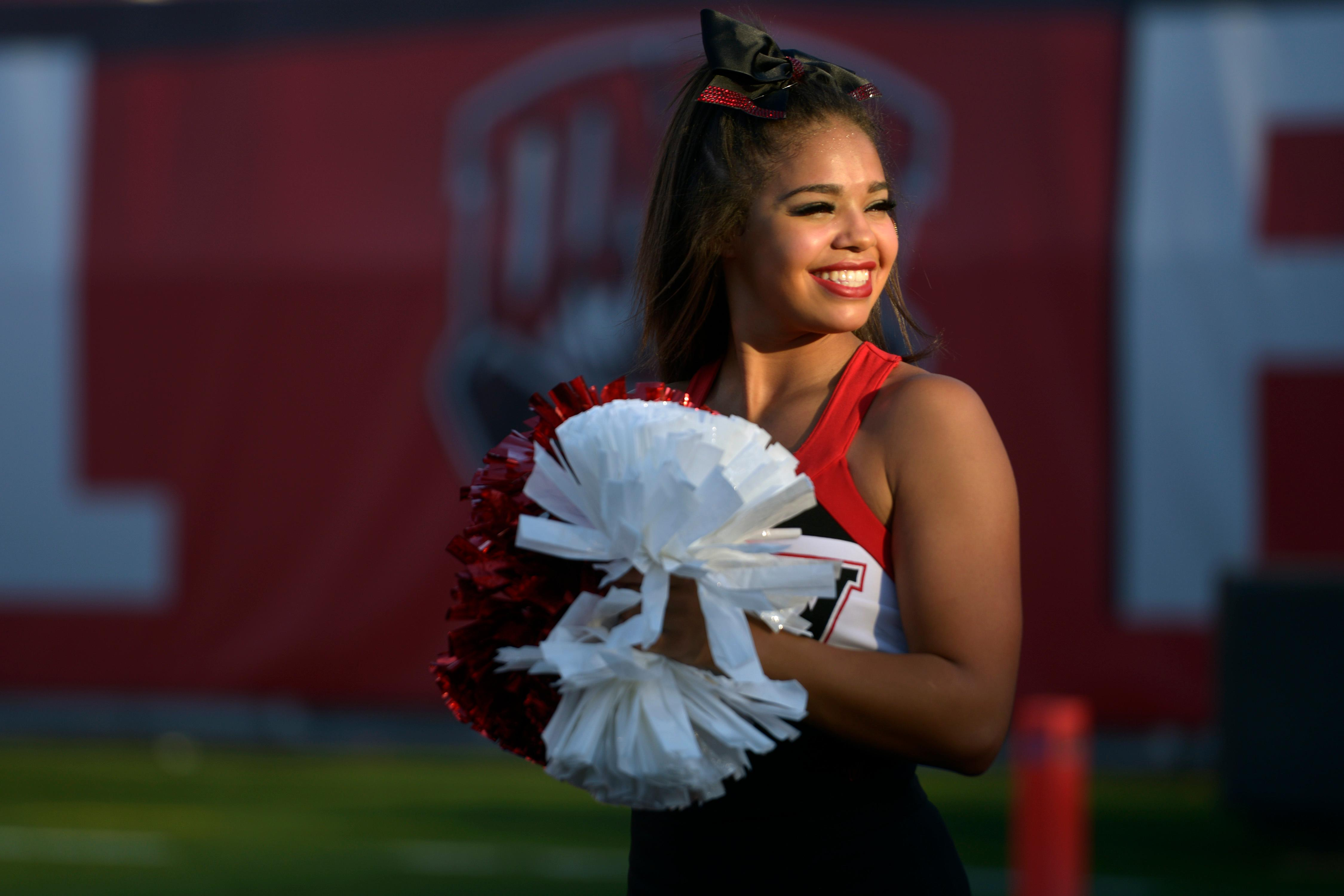 A UNLV cheerleader is illuminated by late afternoon light before their game against Howard University Saturday, September 2, 2017, at Sam Boyd Stadium in Las Vegas. Howard defeated UNLV 43-40 to notch what is believed to be the biggest upset in college football history. [Sam Morris/Las Vegas News Bureau]