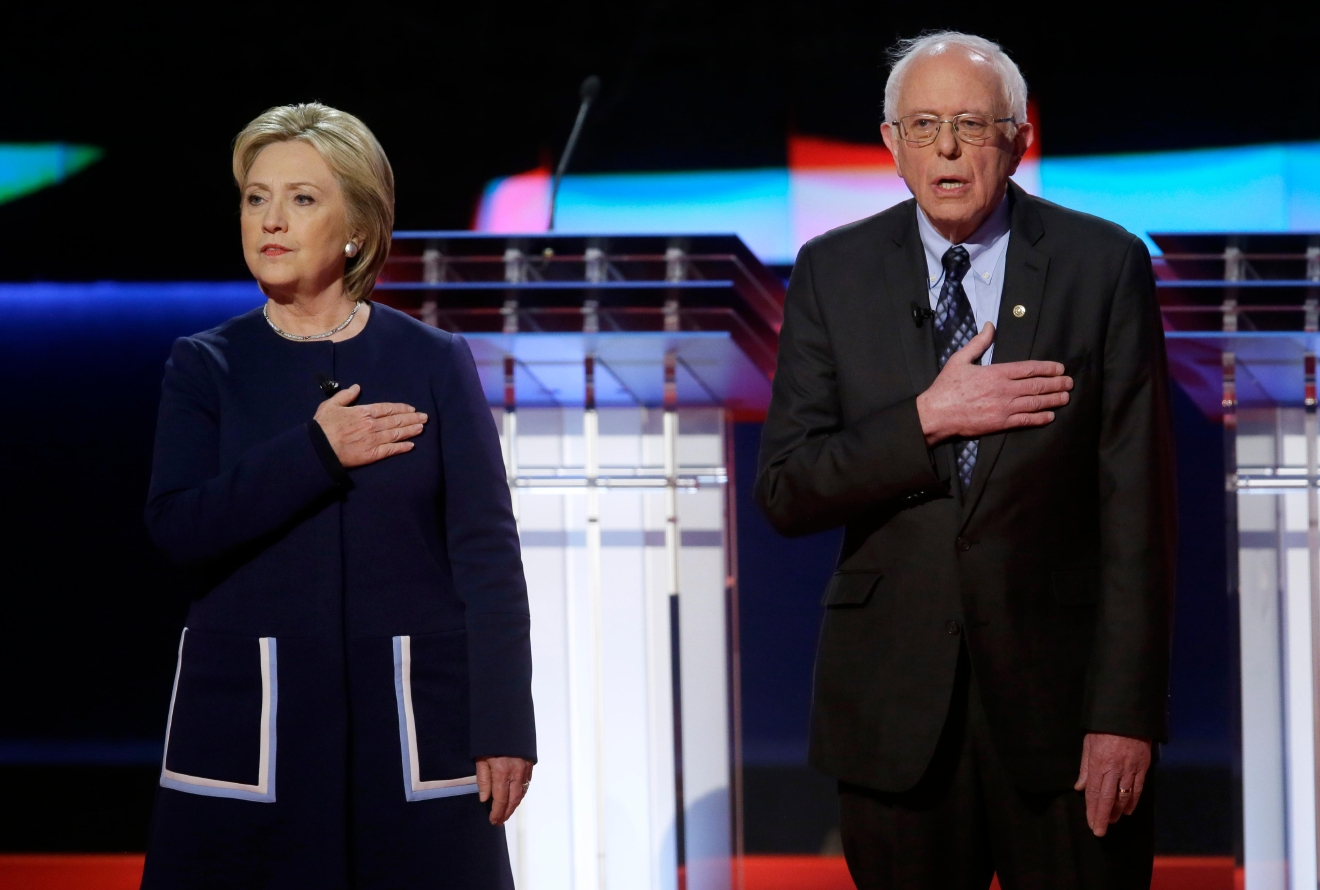Democratic presidential candidates Hillary Clinton, left, and Sen. Bernie Sanders, I-Vt., stand on stage during the National Anthem before a Democratic presidential primary debate at the University of Michigan-Flint, Sunday, March 6, 2016, in Flint, Mich. (AP Photo/Carlos Osorio)