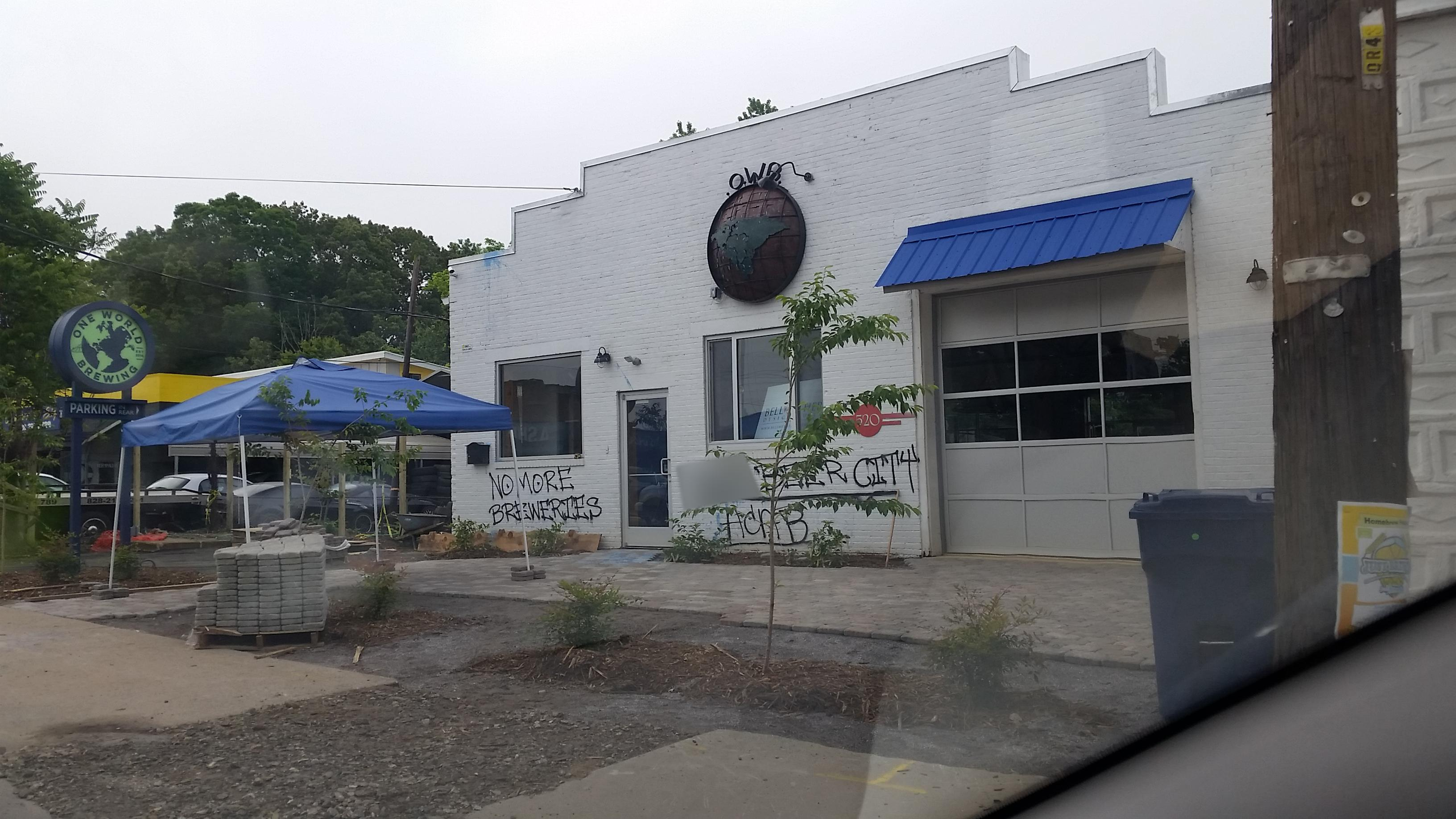 """Seen Around Asheville"" took photos of graffiti scrawled on the exterior of One World Brewing on Haywood Road on Wednesday, May 23. (Photo credit: Seen Around Asheville)"