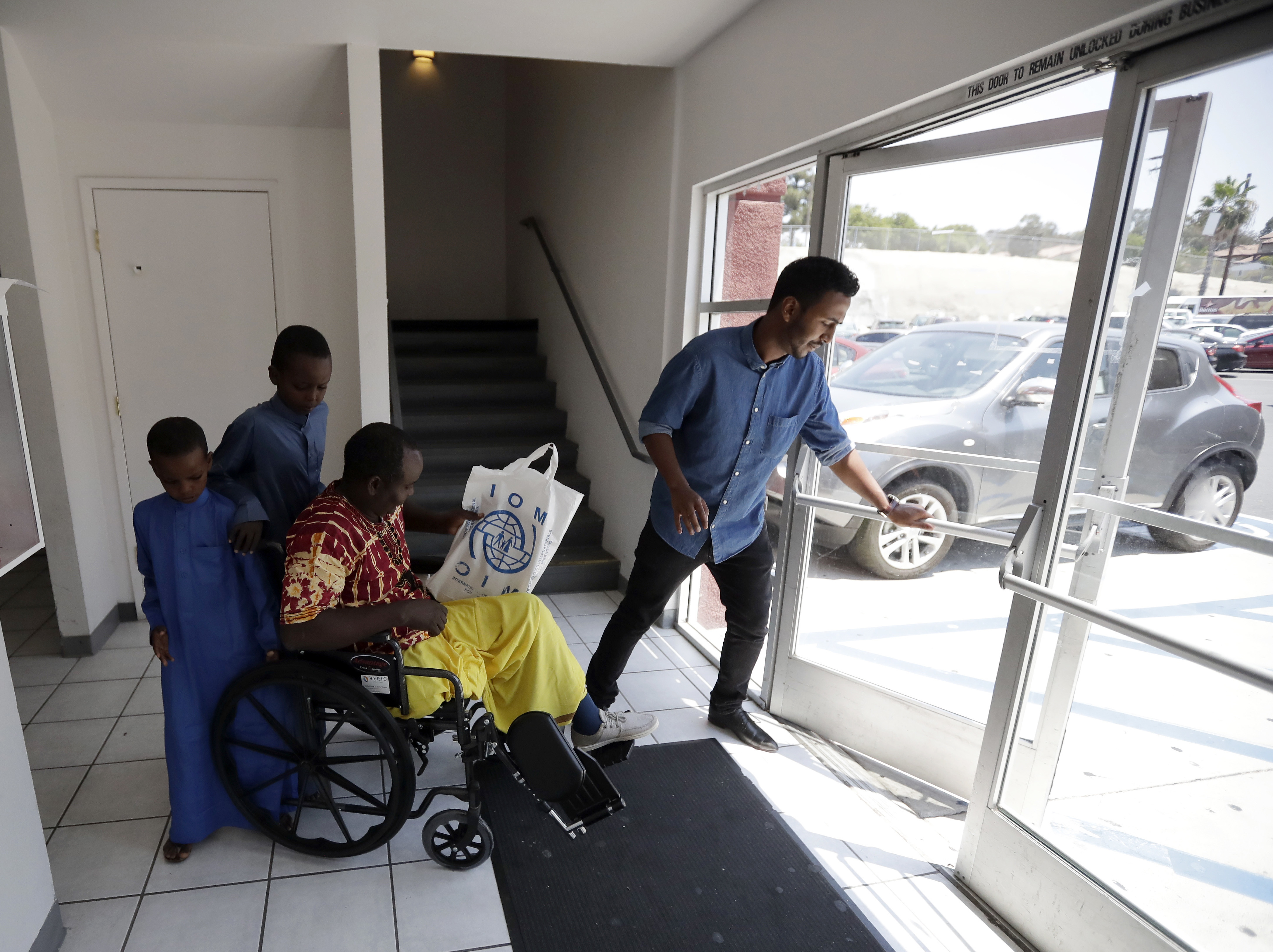 FILE - In this July 6, 2017, file photo, Ali Said, of Somalia, center, leaves a center for refugees with his two sons, as refugee caseworker Mohamed Yassin, right, holds open the door in San Diego. A federal judge in Hawaii further weakened the already-diluted travel ban Thursday, July 13, 2017, by vastly expanding the list of U.S. family relationships that visitors from six Muslim-majority countries can use to get into the country. (AP Photo/Gregory Bull, File)