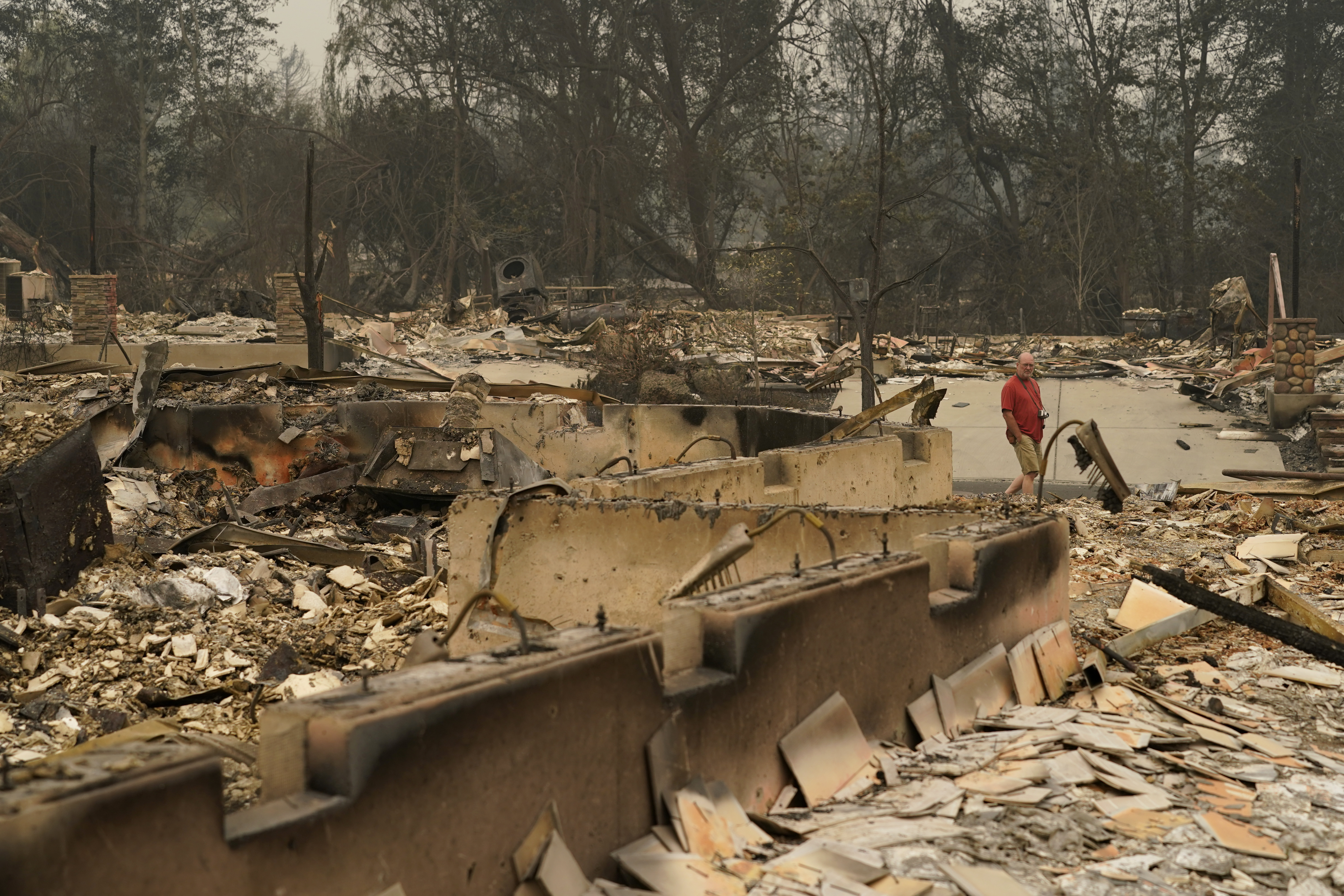 A man walks through a neighborhood destroyed by the Almeda Fire, Friday, Sept. 11, 2020, in Talent, Ore. (AP Photo/John Locher)