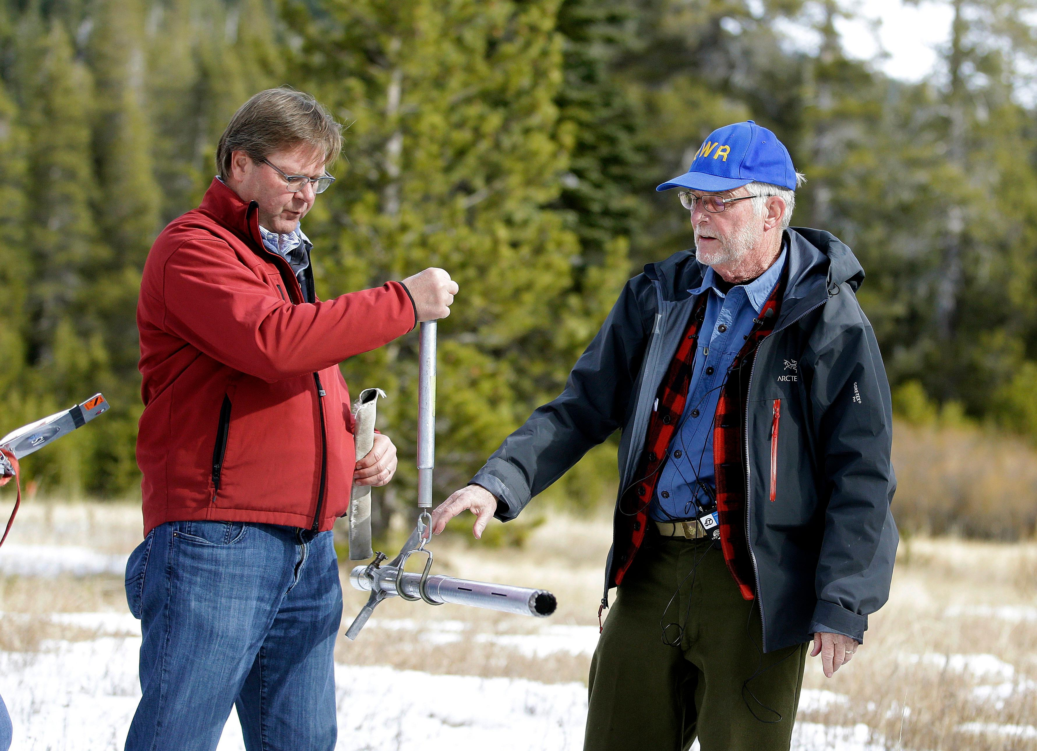 Frank Gehrke, chief of the California Cooperative Snow Surveys Program for the Department of Water Resources, right, checks the weight of the snow survey sample on a scale held by Grant Davis, director of the Dept. of Water Resources, while conducting the first snow survey of the season at the Phillips Station snow course, Wednesday, Jan. 3, 2018, near Echo Summit, Calif.  (AP Photo/Rich Pedroncelli)