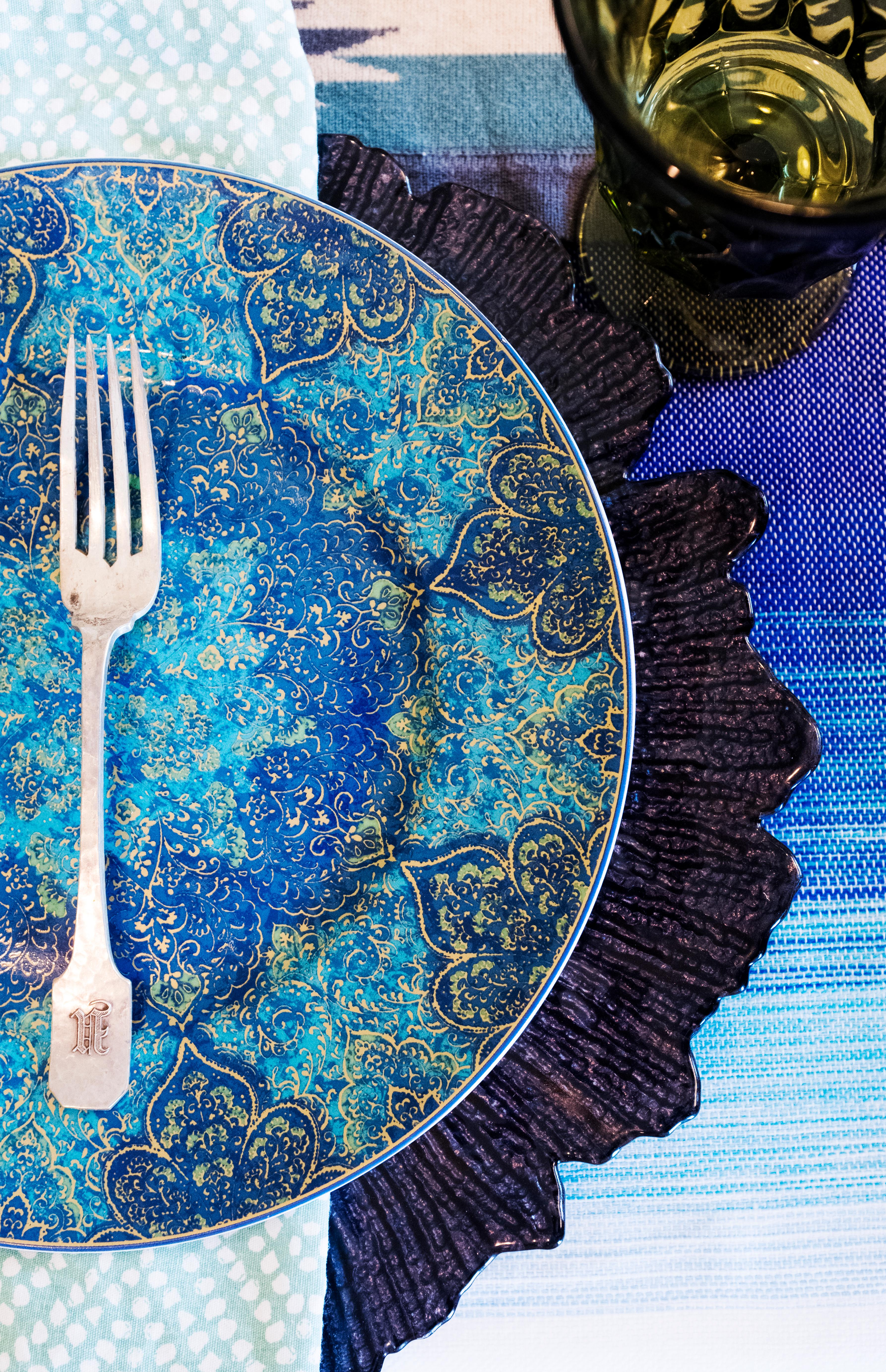 Layer different patterned tablecloths on top of each other and mix and match your napkins for a fun and festive feel. The key to pattern mixing is to stick to a basic color palate such as green, blue, and white. Then mix large patterns with small or medium patterns to avoid a busy look.(Image: Ashley Hafstead)