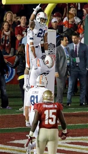 Auburn's Chad Slade lifts teammate Tre Mason after Mason 's touchdown run during the first half of the NCAA BCS National Championship college football game against Florida State Monday, Jan. 6, 2014, in Pasadena, Calif.