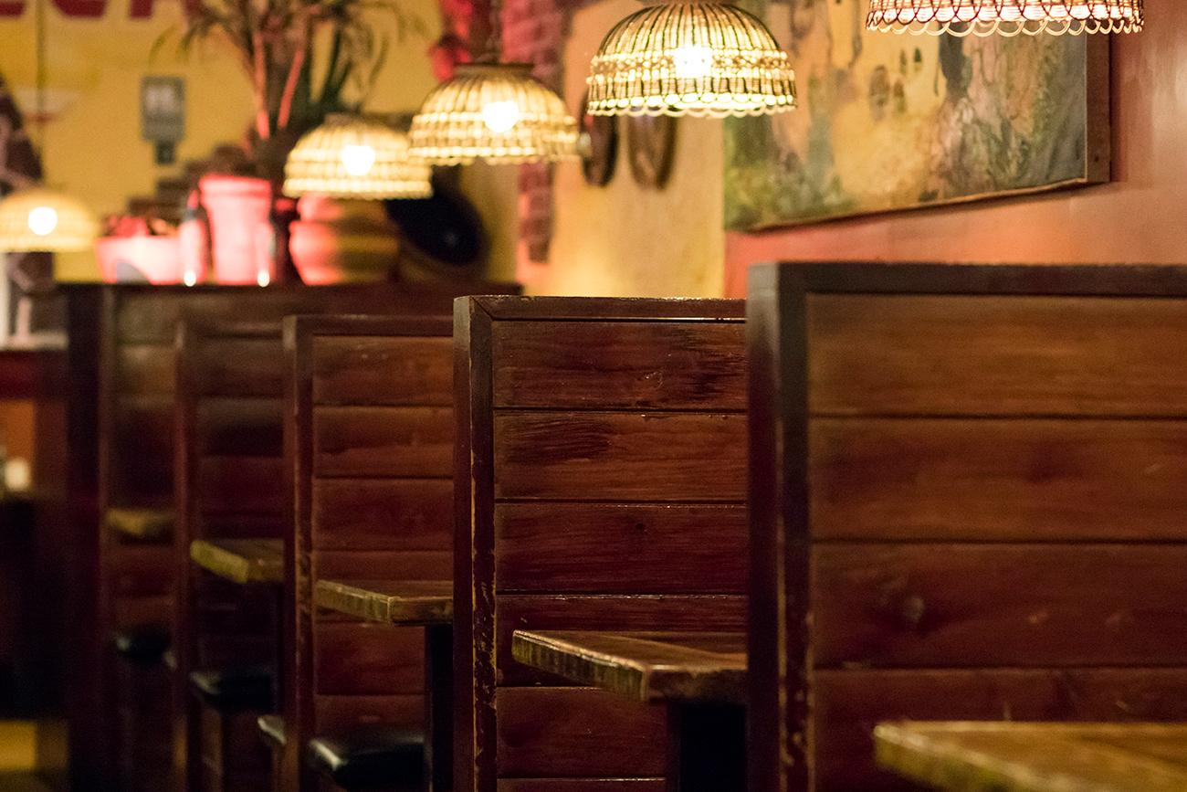 The dark, high-backed booths and original artwork by artist Villatana from Tulsa Jalisco Mexico enhance the golden stucco walls. / Image: Allison McAdams // Published: 5.1.18