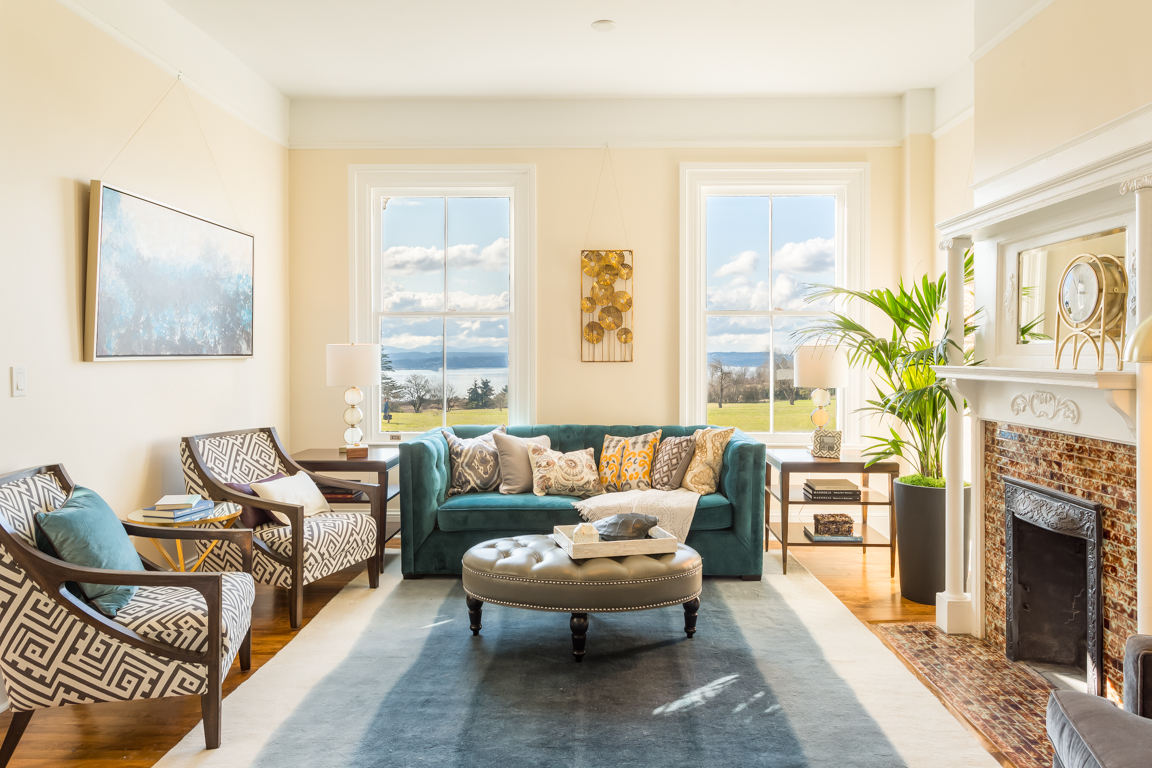 The Frederick's spacious first floor living room holds one of the home's many original fire places and showcases view of Discovery Park, the Puget Sound, and the Olympic Mountains.