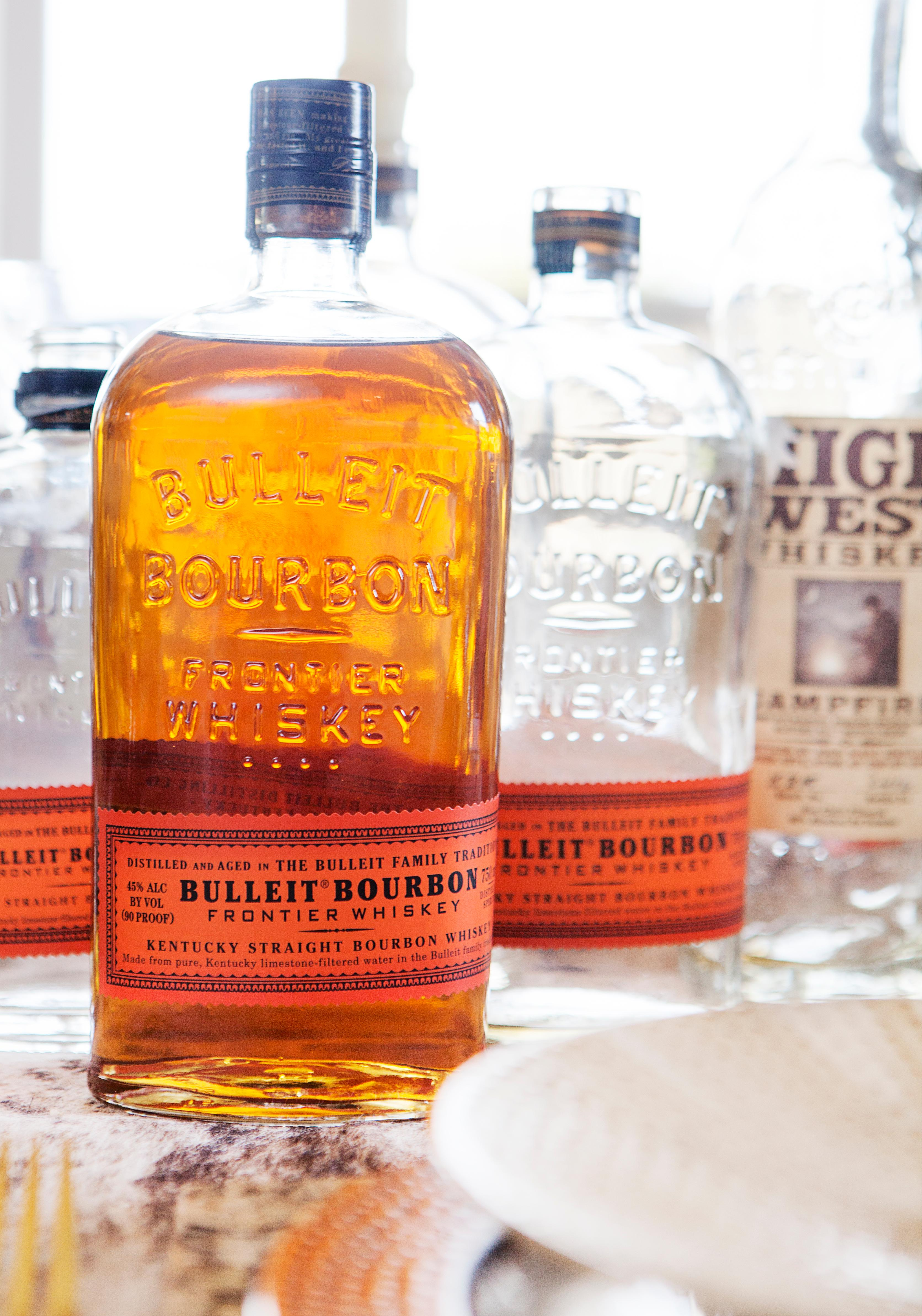 You can't just have empty bourbon bottles down the center of the table! Add a full bottle of bourbon for your guests to enjoy during dinner. (Image: Ashley Hafstead)