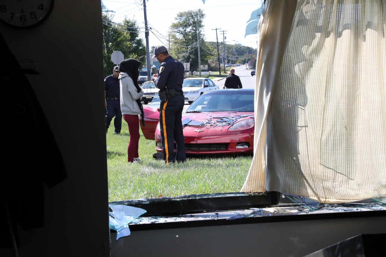 The driver of a car that hit The Press of Atlantic City business and editorial office and crashed the window into the newsroom, talks to police off Washington Avenue, in Pleasantville, N.J., Tuesday, Oct. 17, 2017. (Vernon Ogrodnek/The Press of Atlantic City via AP)