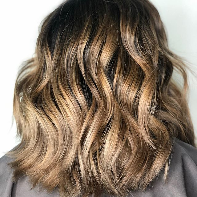 Sunset Ombré: This is balayage highlights on a brunette base, that start further down the hair strand, creating an ombré effect. Around the face, the highlight will start at the scalp to frame and brighten the face. The maintenance for this look would include color every 10 weeks, and the client should ask for neutral-colored ombré highlights with bright, face-framing highlights. Staying with neutral tones (like a mushroom-tone) looks great on brunettes and tends to keep the hair from appearing brassy. (Image courtesy of Gene Juarez).