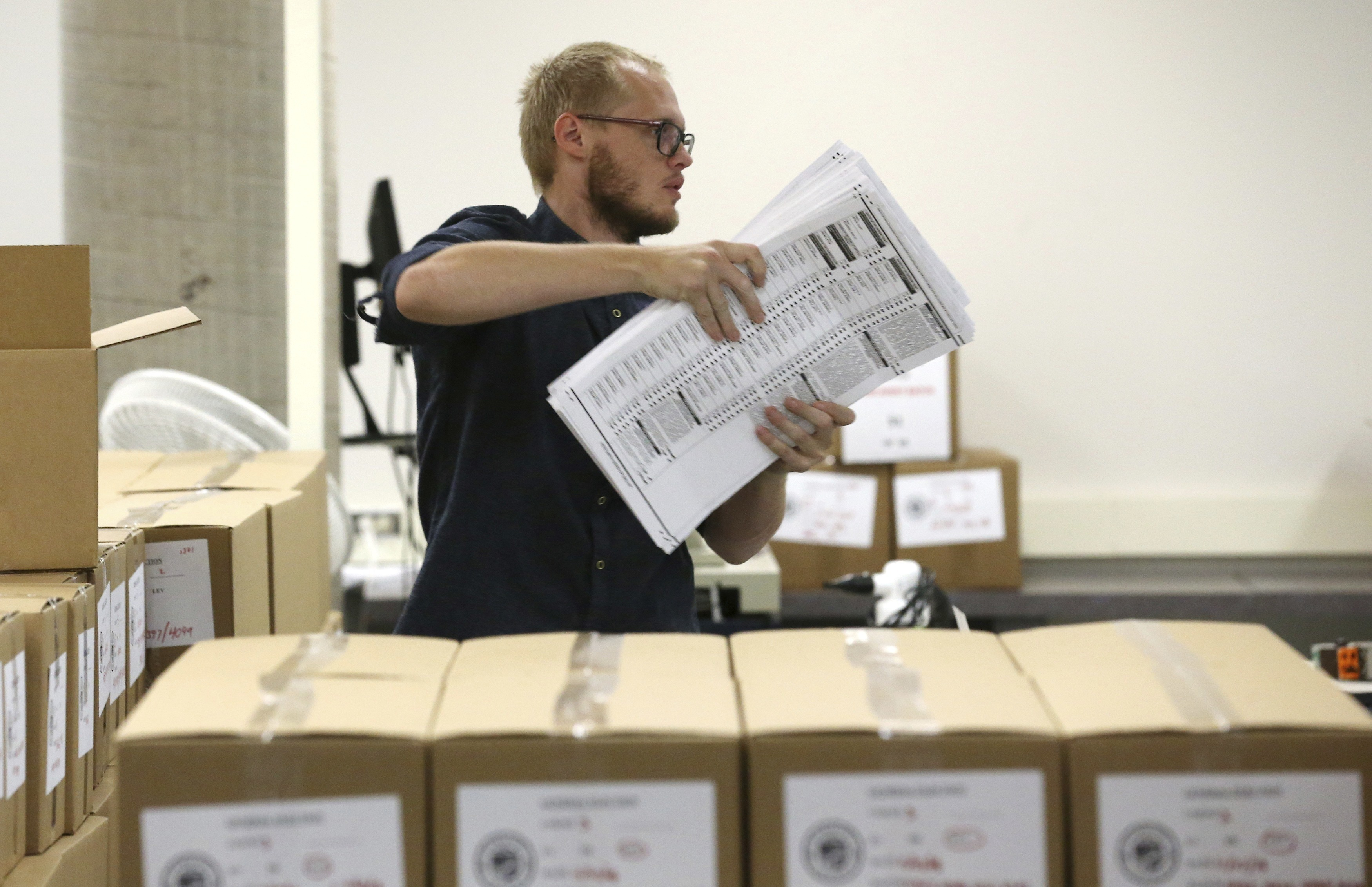 A worker carries ballots to be verified at the Maricopa County Recorder's Office Thursday, Nov. 8, 2018, in Phoenix. (AP Photo/Ross D. Franklin)