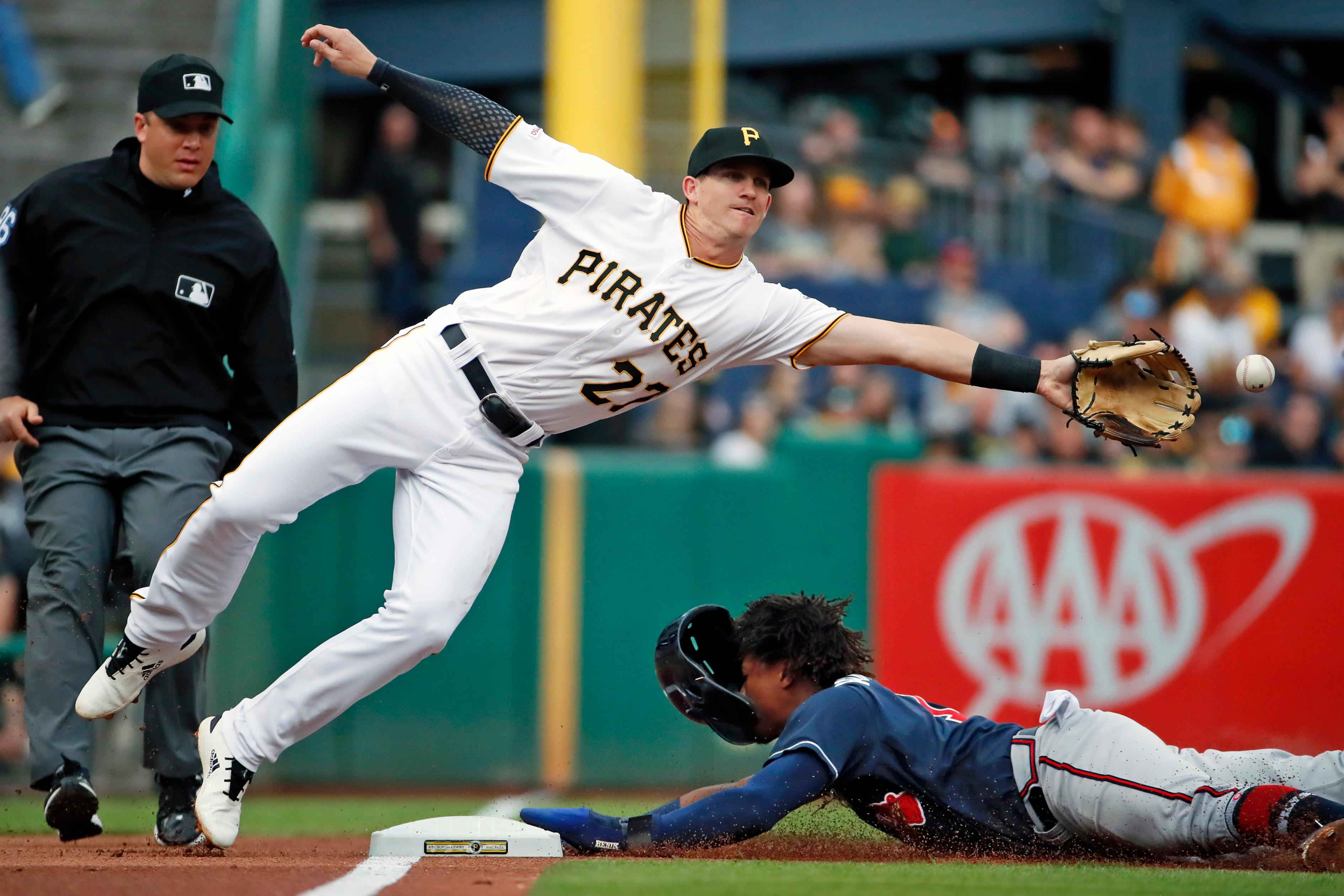 Pittsburgh Pirates third baseman Kevin Newman (27) reaches for but can't reach an errant throw by catcher Elias Diaz as Atlanta Braves' Ronald Acuna Jr. steals third during the first inning of a baseball game in Pittsburgh, Tuesday, June 4, 2019. Acuna scored on the throwing error. (AP Photo/Gene J. Puskar)