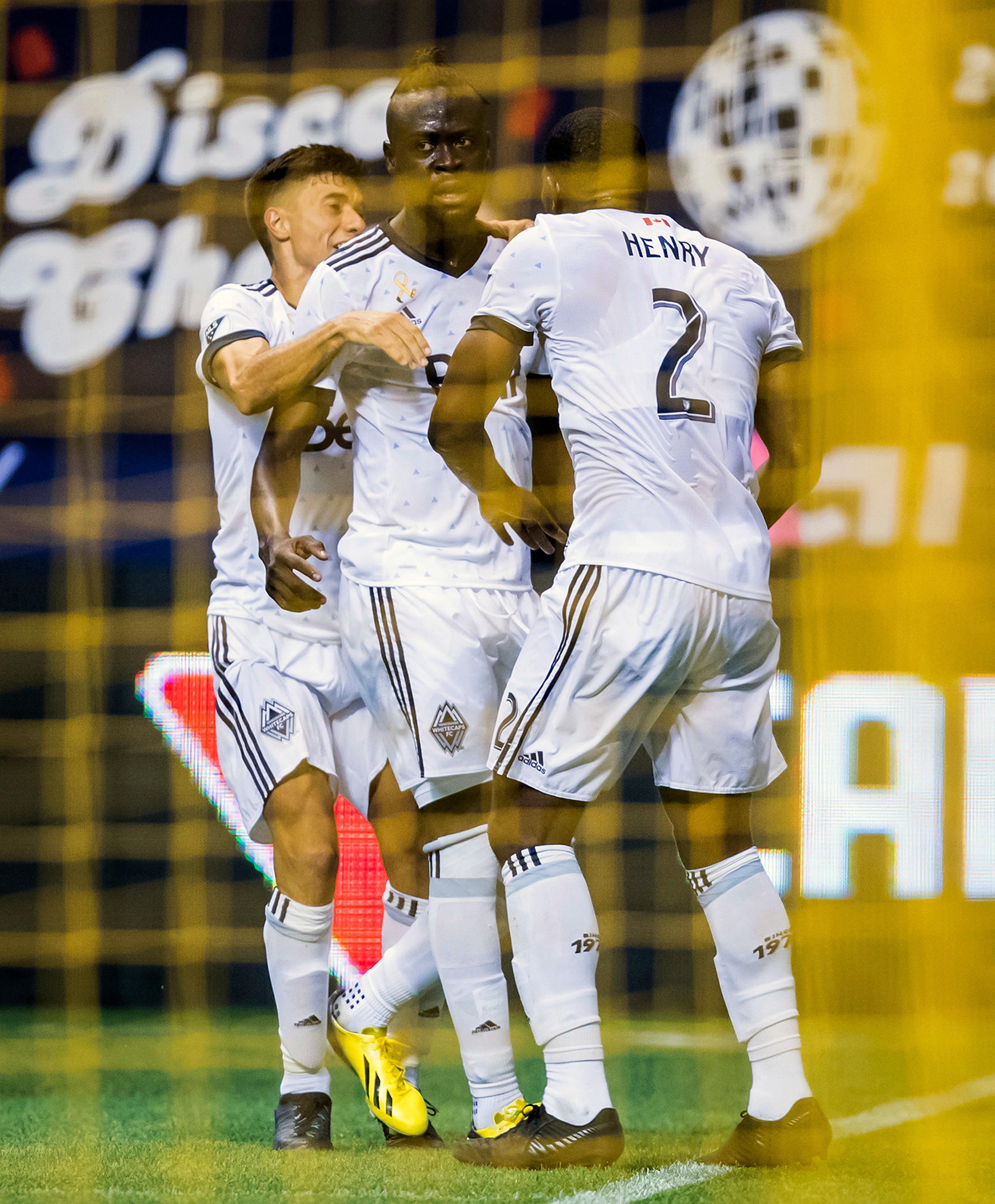 Vancouver Whitecaps' Nicolas Mezquida, from left to right, Kei Kamara and Doneil Henry celebrate Kamara's goal against the Seattle Sounders during the first half of an MLS soccer match, Saturday, Sept. 15, 2018, in Vancouver, British Columbia. (Darryl Dyck/The Canadian Press via AP)