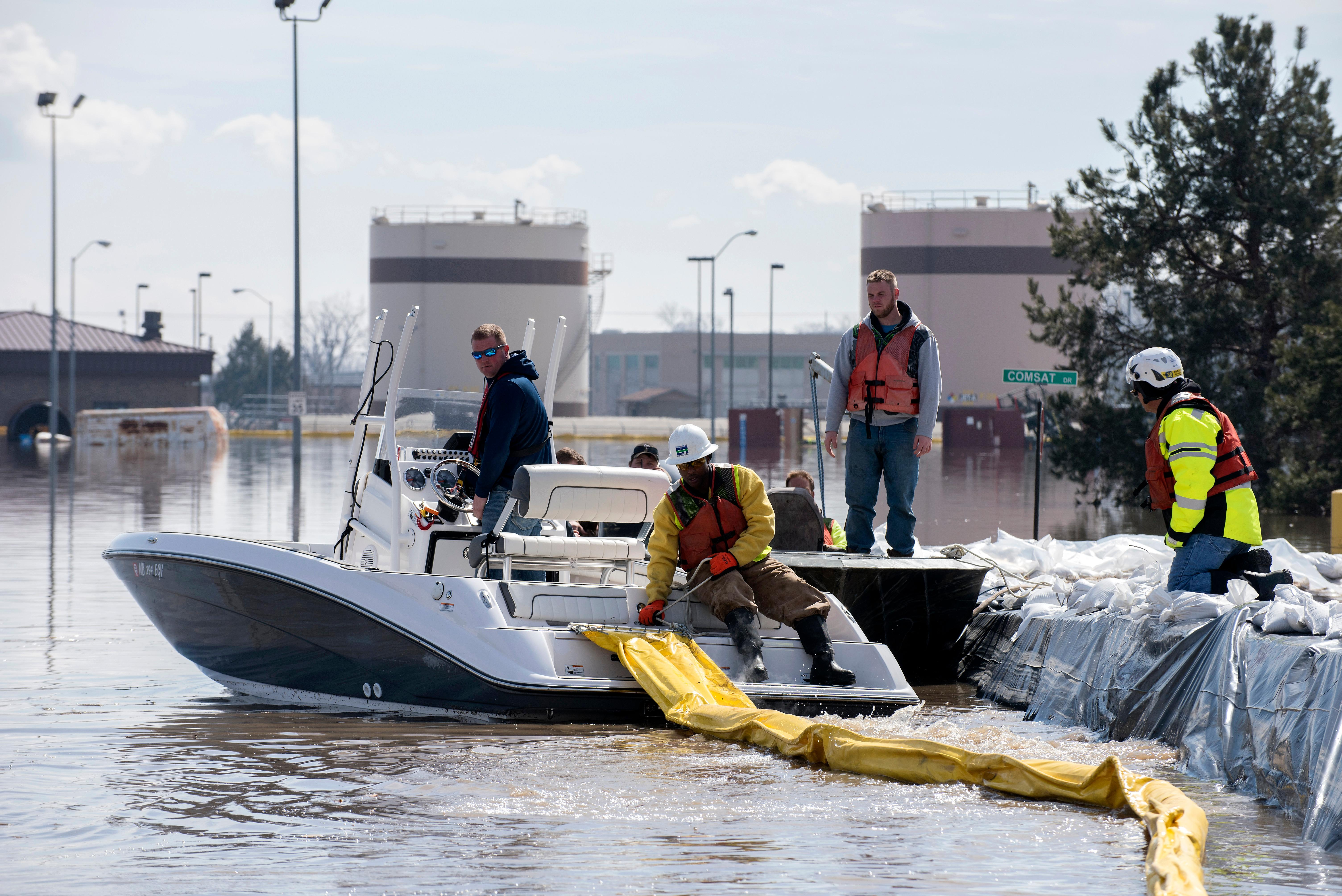 In this March 18, 2019 photo released by the U.S. Air Force, environmental restoration employees deploy a containment boom from a boat on Offutt Air Force Base in Neb., as a precautionary measure for possible fuel leaks in the flooded area. (Delanie Stafford, The U.S. Air Force via AP)