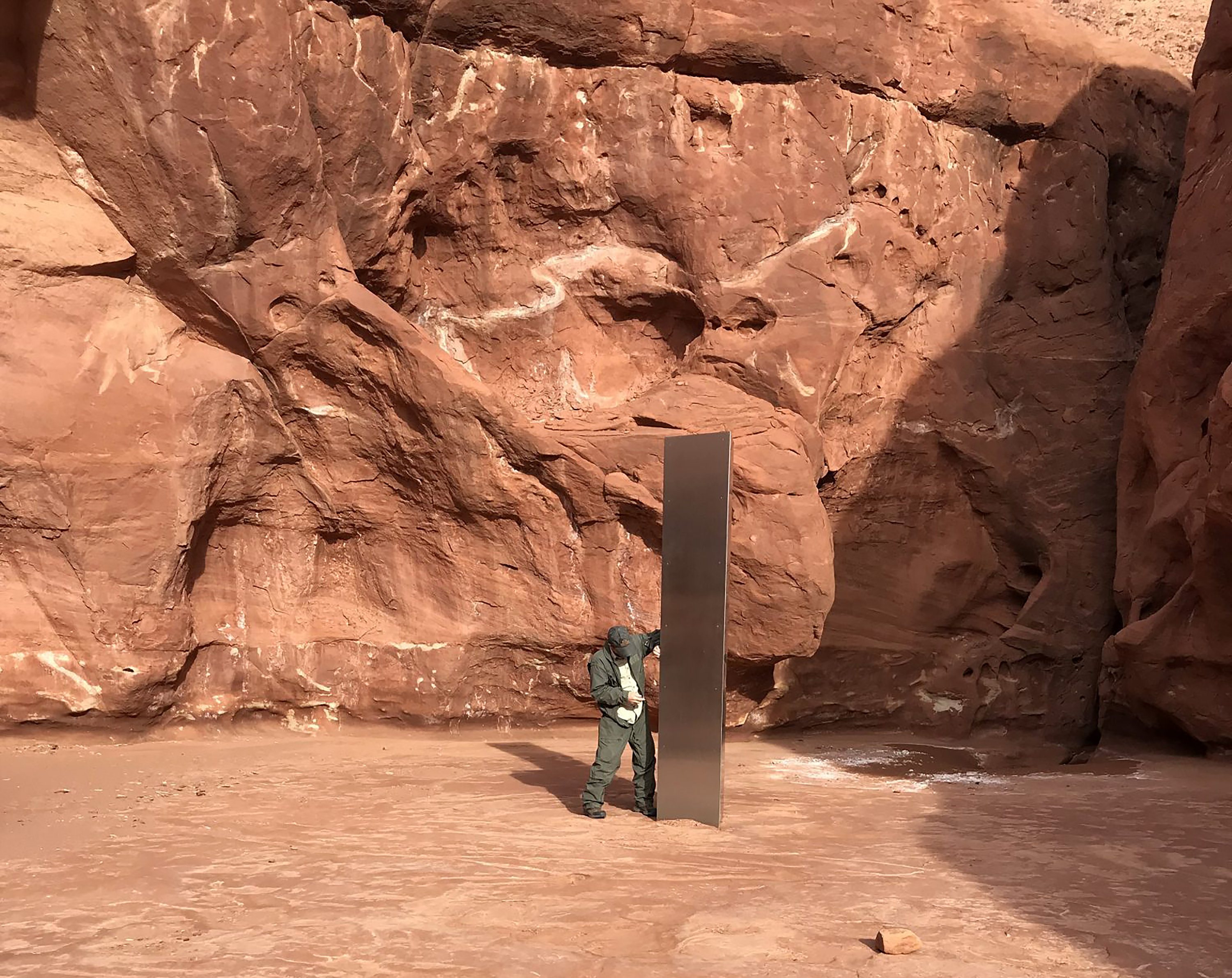 In this Nov. 18, 2020, file photo provided by the Utah Department of Public Safety, a Utah state worker stands next to a metal monolith in the ground in a remote area of red rock in Utah. The mysterious silver monolith that was placed in the Utah desert has disappeared less than 10 days after it was spotted by wildlife biologists performing a helicopter survey of bighorn sheep, federal officials and witnesses said. The Bureau of Land Management said it had received credible reports that the three-sided stainless steel structure was removed on Nov. 27.  (Utah Department of Public Safety via AP, File)