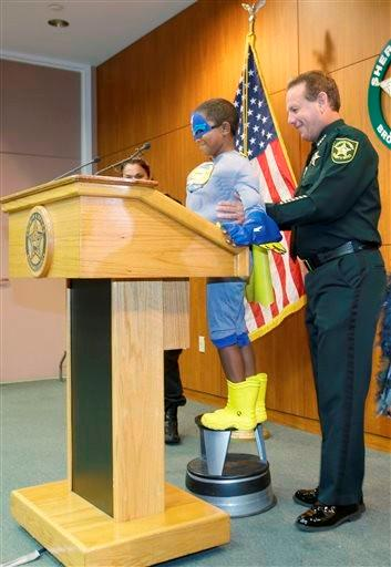Broward County Sheriff Scott Israel, right, helps up onto a stool so he can reach the podium, Jaylen Hyde, aka %u201CStriker Boy,%u201D before giving a joint news conference at the Broward Sheriff's Office in Fort Lauderdale, Fla Friday, June 6, 2014.