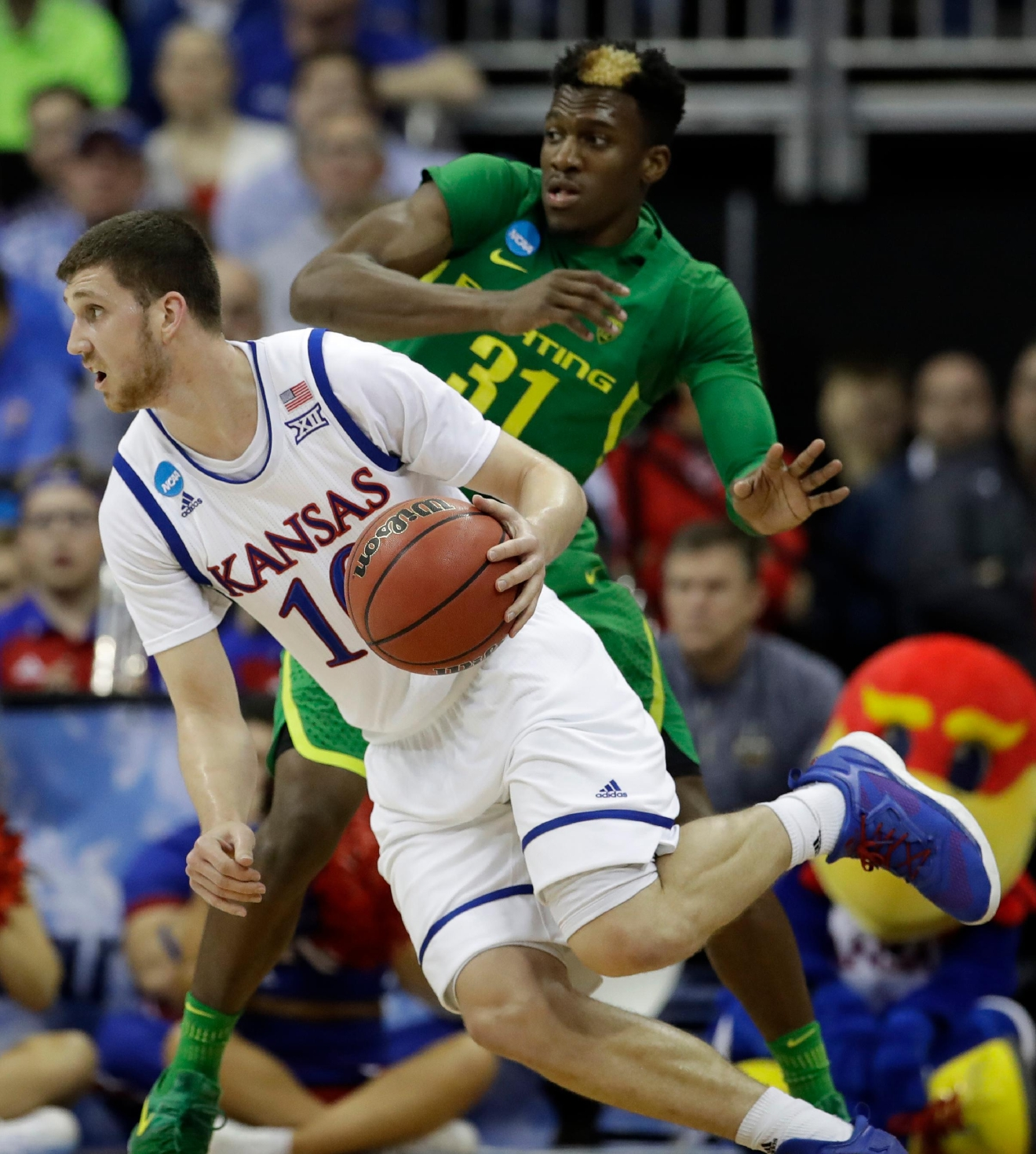 Kansas guard Sviatoslav Mykhailiuk drives around Oregon guard Dylan Ennis (31) during the second half of the Midwest Regional final of the NCAA men's college basketball tournament, Saturday, March 25, 2017, in Kansas City, Mo. (AP Photo/Charlie Riedel)