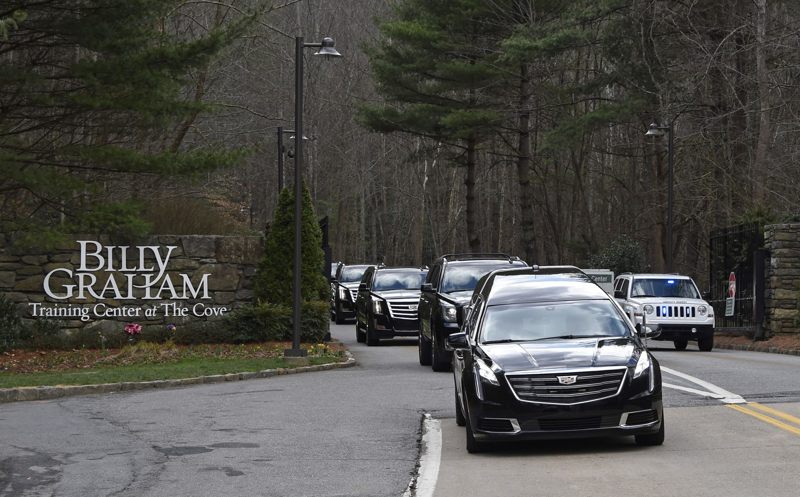 The hearse carrying the body of Billy Graham leaves the Billy Graham Training Center in Asheville, N.C., Saturday, Feb. 24, 2018. Graham's body was brought to his hometown of Charlotte on Saturday, Feb. 24, as part of a procession expected to draw crowds of well-wishers. (Kathy Kmonicek/pool photo)