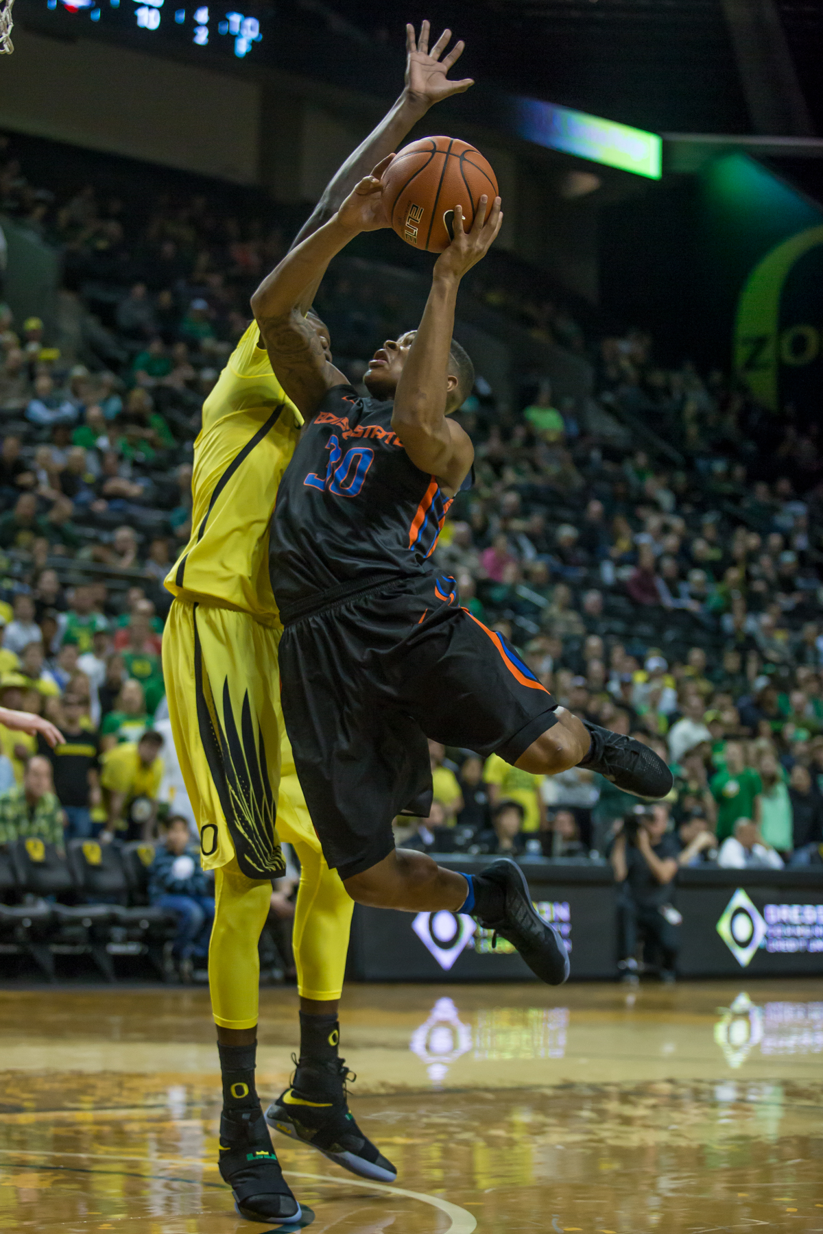 Boise State guard Paris Austin (#30) leans into Oregon forward Chris Boucher (#25) as he shoots a layup. After trailing for most of the game, the Oregon Ducks defeated the Boise State Broncos 68-63. Photo by Dillon Vibes