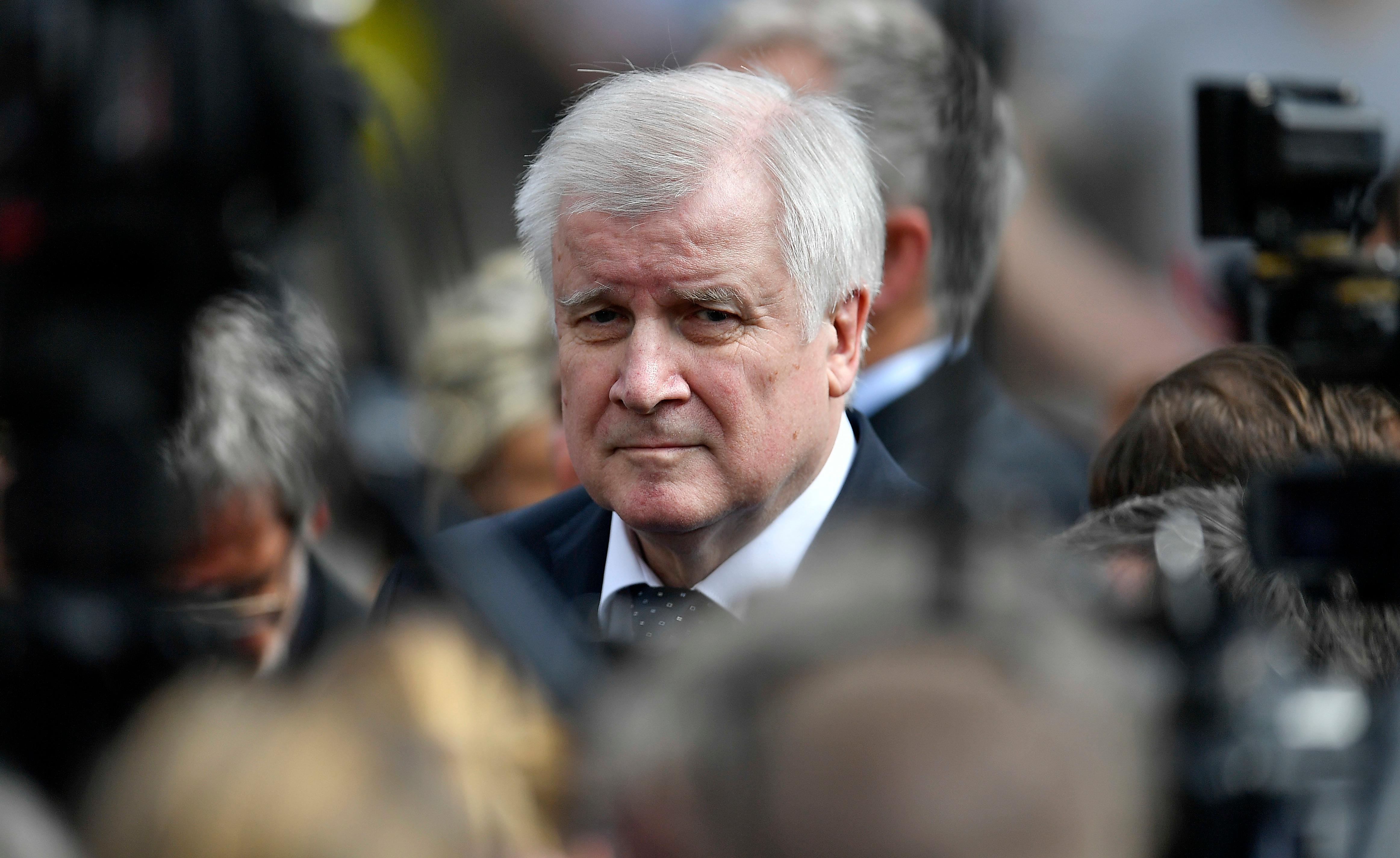 German interior minister Horst Seehofer visits the place in Muenster, Germany, Sunday, April 8, 2018 where a vehicle crashed into a crowd yesterday. A van crashed into people drinking outside a popular bar Saturday in the German city of Muenster, killing two people and injuring 20 others before the driver of the vehicle shot and killed himself inside it, police said. (AP Photo/Martin Meissner)