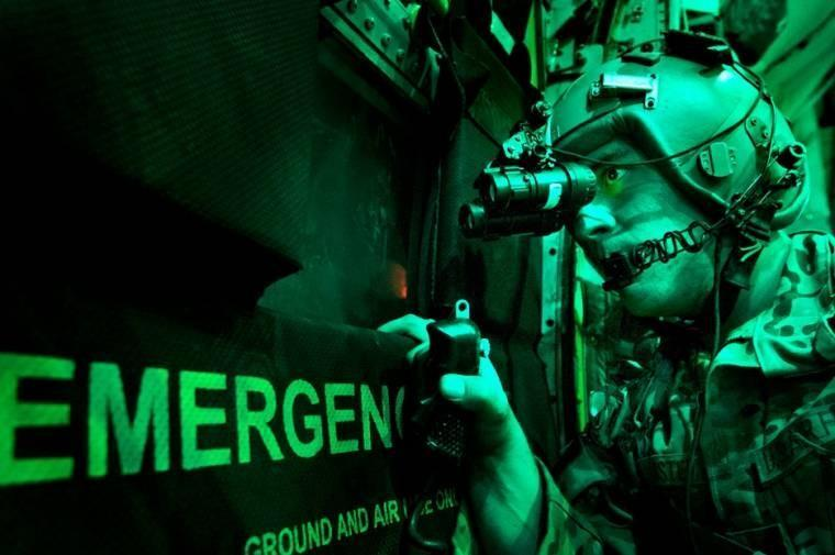 As seen through a night-vision device, U.S Senior Airman Larry Webster scans for potential threats using night-vision goggles after completing a cargo airdrop in Ghazni province, Afghanistan.