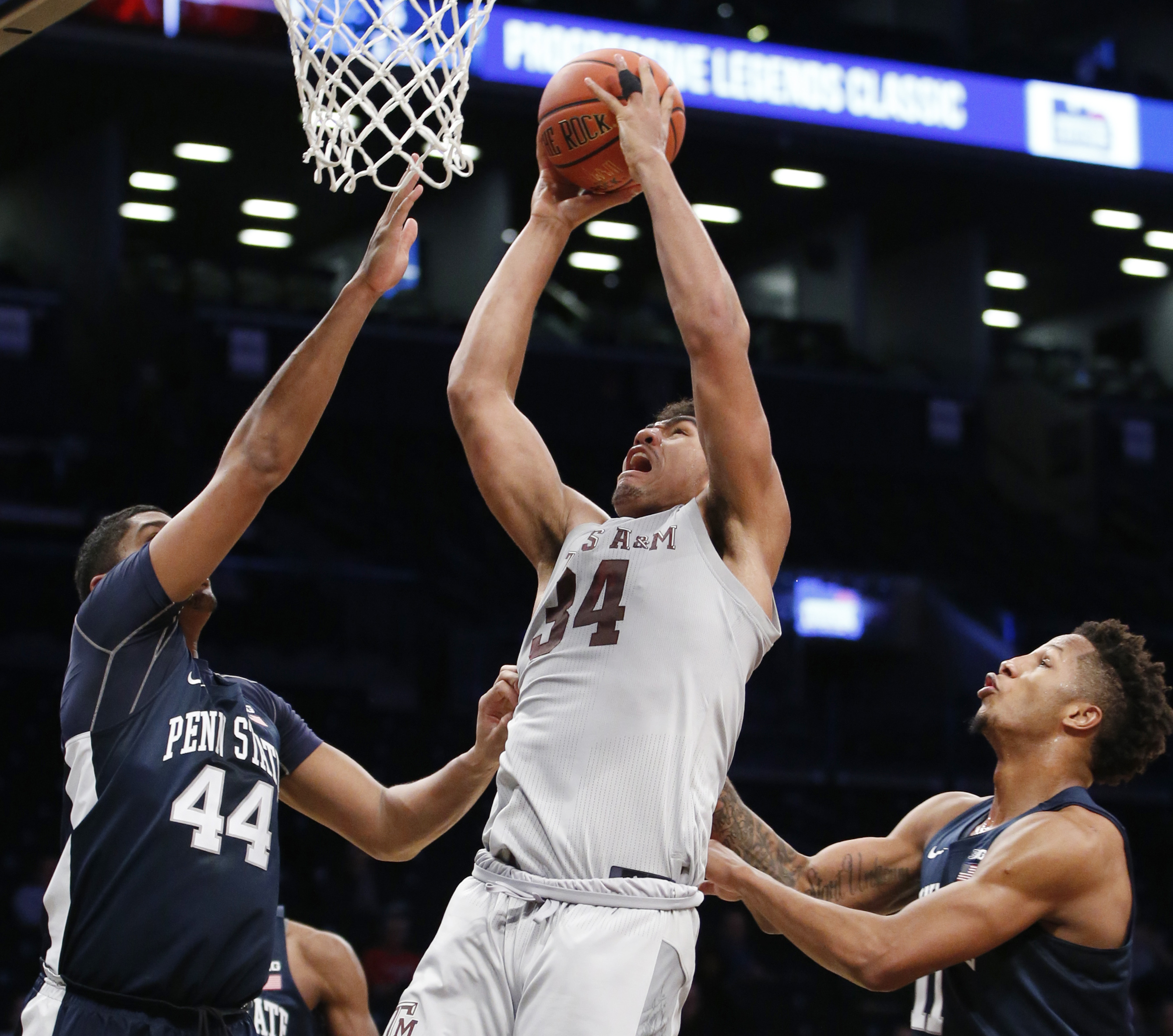 Penn State forward Julian Moore, left,  and teammate Lamar Stevens, right,  defend as Texas A&M center Tyler Davis, center,  takes a shot during the first half of an NCAA college basketball game in the Legends Classic tournament, Tuesday, Nov. 21, 2017, in New York. (AP Photo/Kathy Willens)