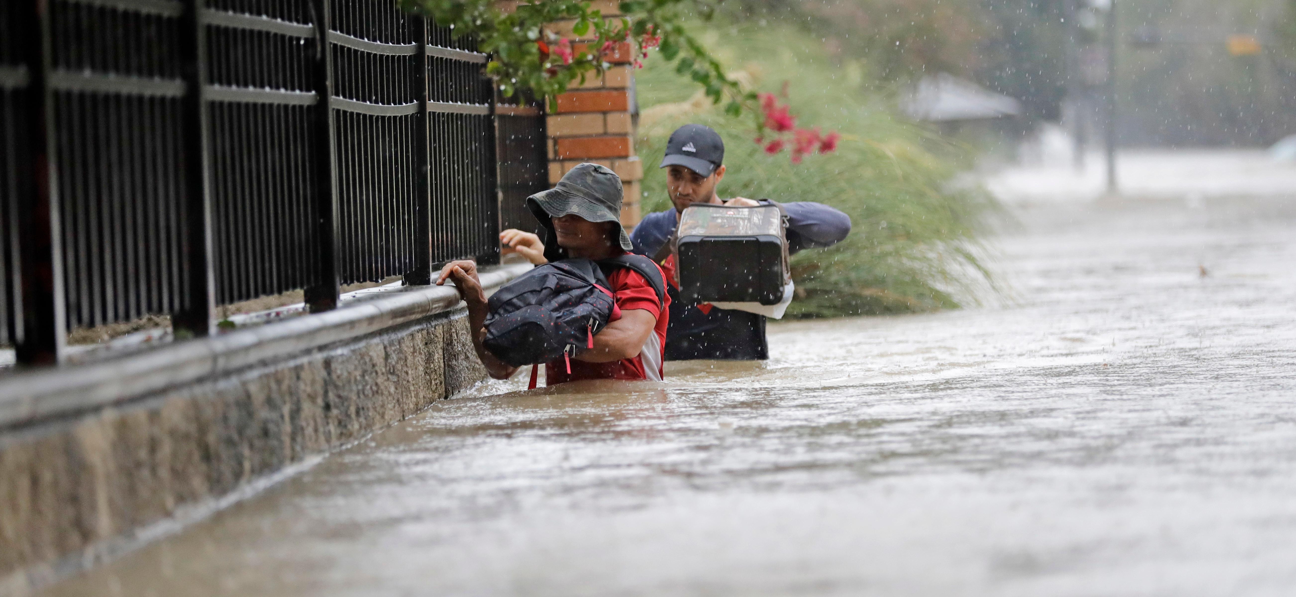 Residents wade through floodwaters from Tropical Storm Harvey Sunday, Aug. 27, 2017, in Houston, Texas. (AP Photo/David J. Phillip)