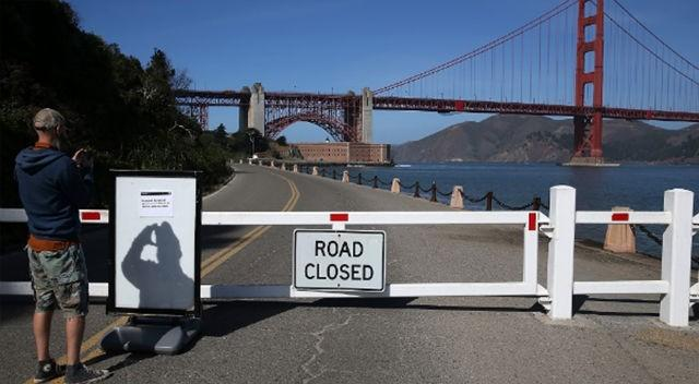 A visitor takes a picture of a sign announcing the closure of the Fort Point National Historic Site due to the partial government shutdown on October 1 in San Francisco, California.