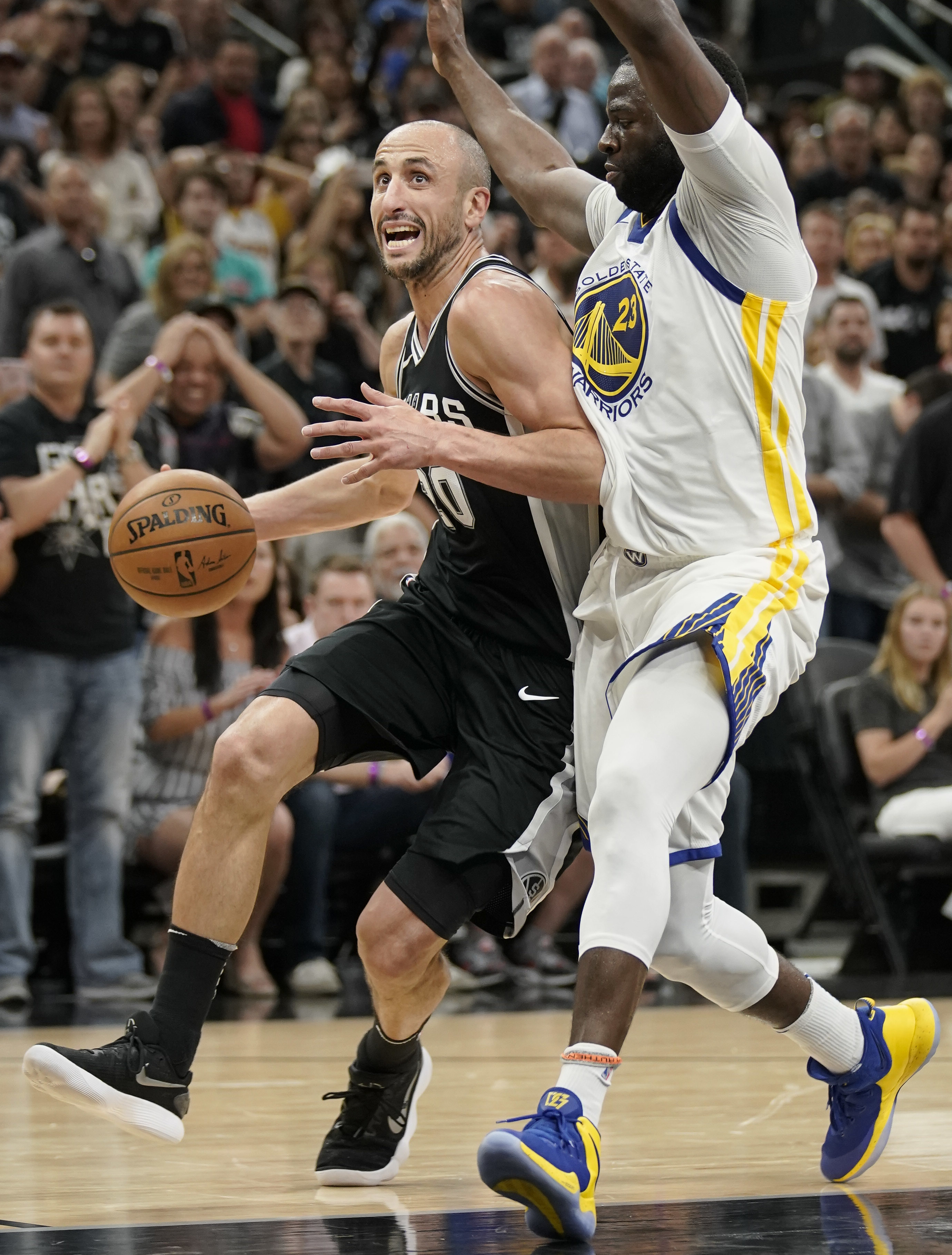 San Antonio Spurs' Manu Ginobili, left, drives against Golden State Warriors' Draymond Green during the second half of Game 4 of a first-round NBA basketball playoff series in San Antonio, Sunday, April 22, 2018, in San Antonio. San Antonio won 103-90. (AP Photo/Darren Abate)