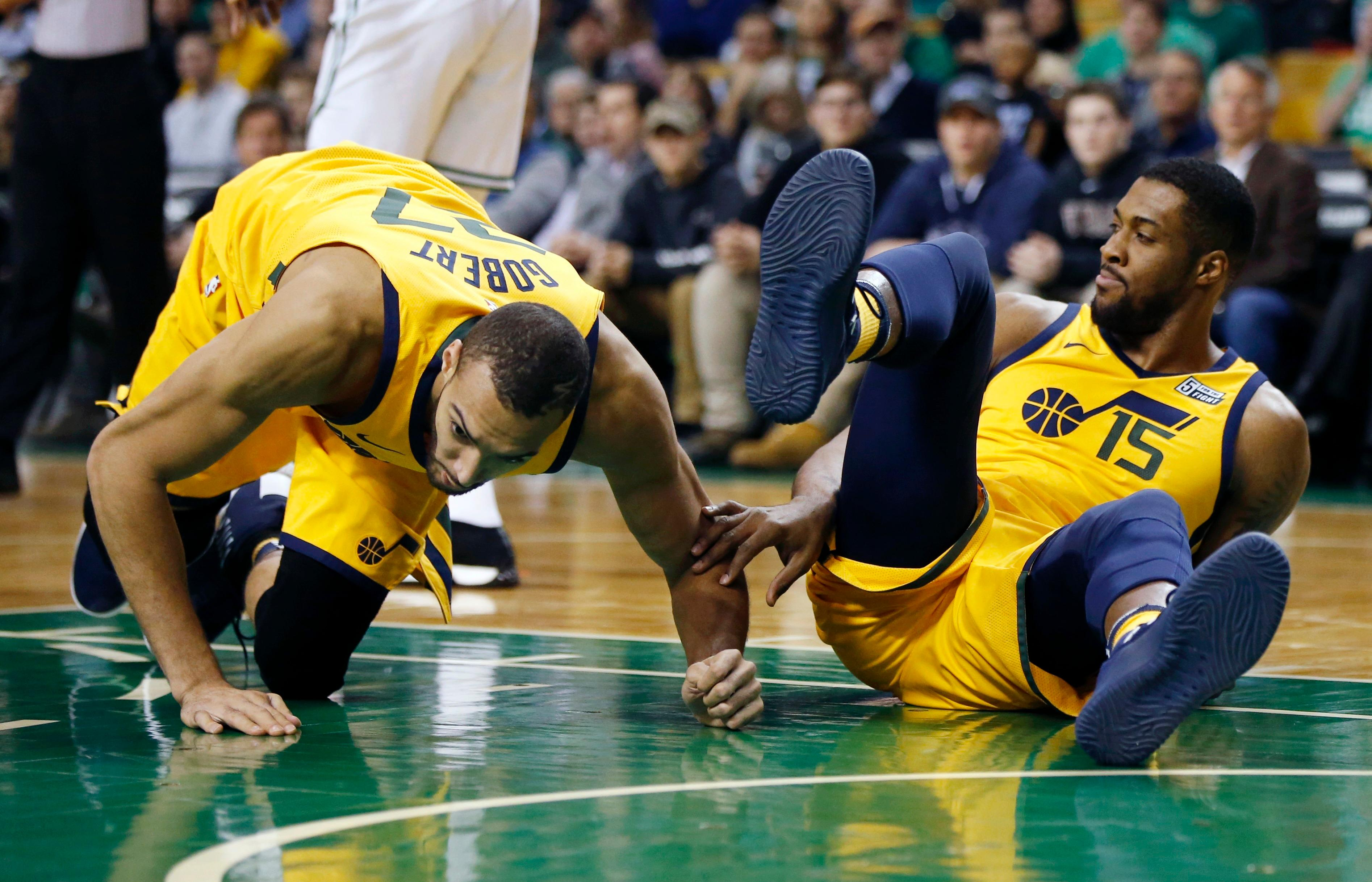 Utah Jazz's Rudy Gobert (27) kneels on the floor beside teammate Derrick Favors (15) during the first quarter of an NBA basketball game against the Boston Celtics in Boston, Friday, Dec. 15, 2017. Gobert left the game with a knee injury after Favors fell backward into his leg on the play. (AP Photo/Michael Dwyer)