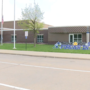 Worker at Sunrise Middle says thank you, goodbye with sign in school's front lawn