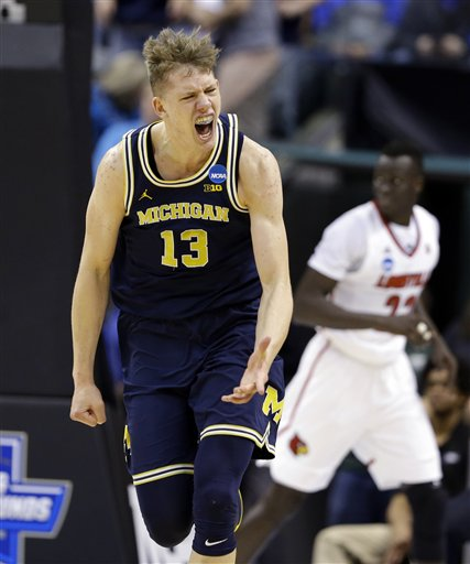 Michigan forward Moritz Wagner (13) celebrates a basket against Louisville  during the first half of a second-round game in the mens NCAA college basketball tournament in Indianapolis, Sunday, March 19, 2017. (AP Photo/Michael Conroy)