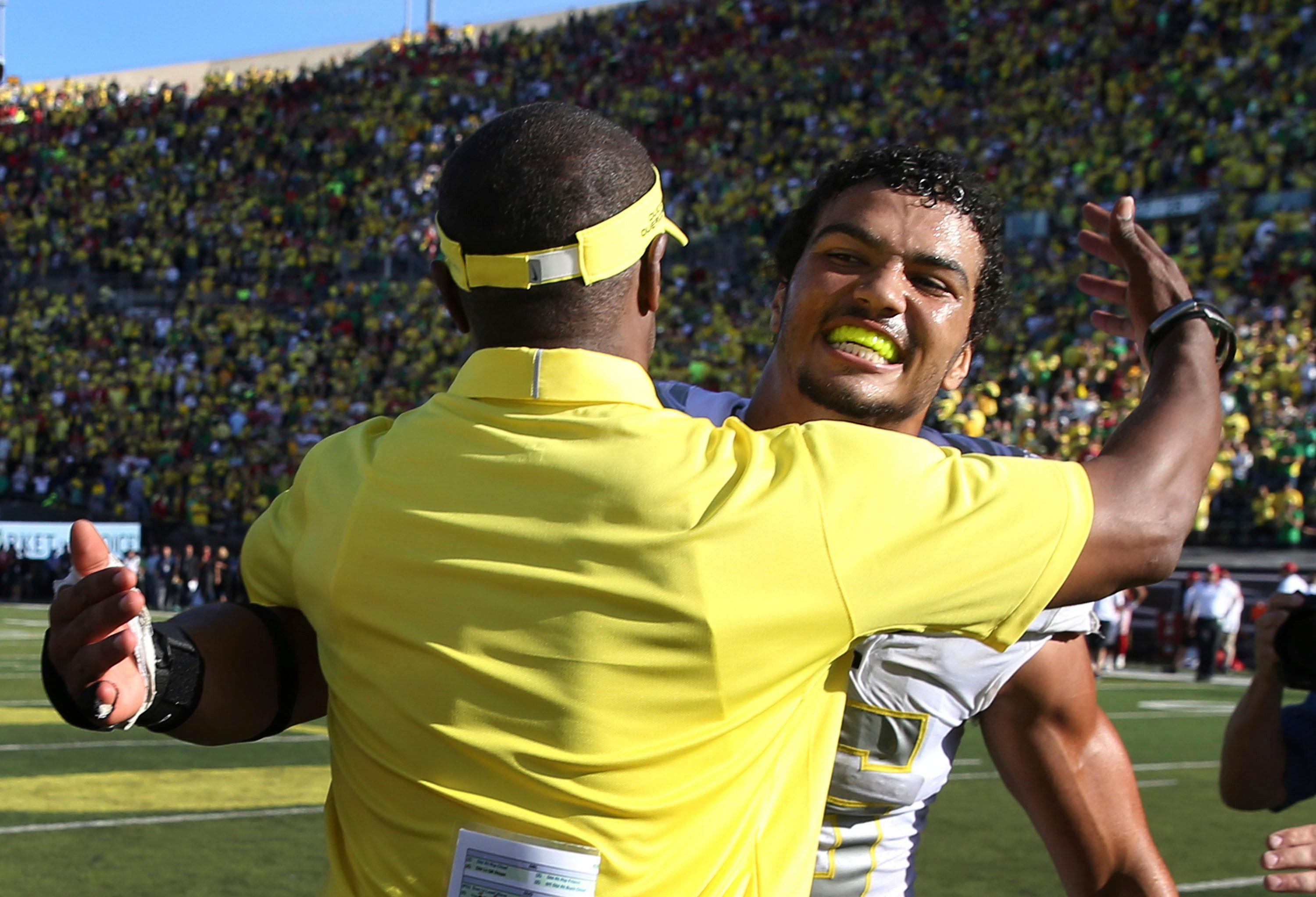 FILE - In this Sept. 9, 2017, file photo, Oregon head coach Willie Taggart and linebacker Troy Dye, rear, embrace after defeating Nebraska, 42-35, in an NCAA college football game, in Eugene, Ore. Dye was selected to the AP All-Conference Pac-12 team announced Thursday, Dec. 7, 2017. (AP Photo/Chris Pietsch, File)