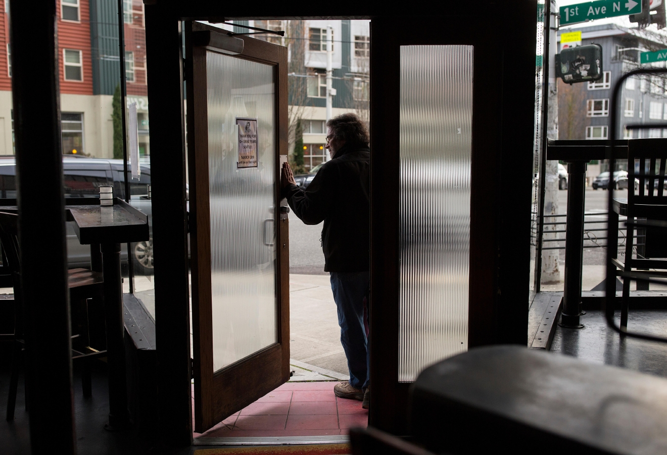 A patron exits the bar during Tini Bigs Lounge's final day of business after having served the Seattle community for over 20 years. (Sy Bean / Seattle Refined)