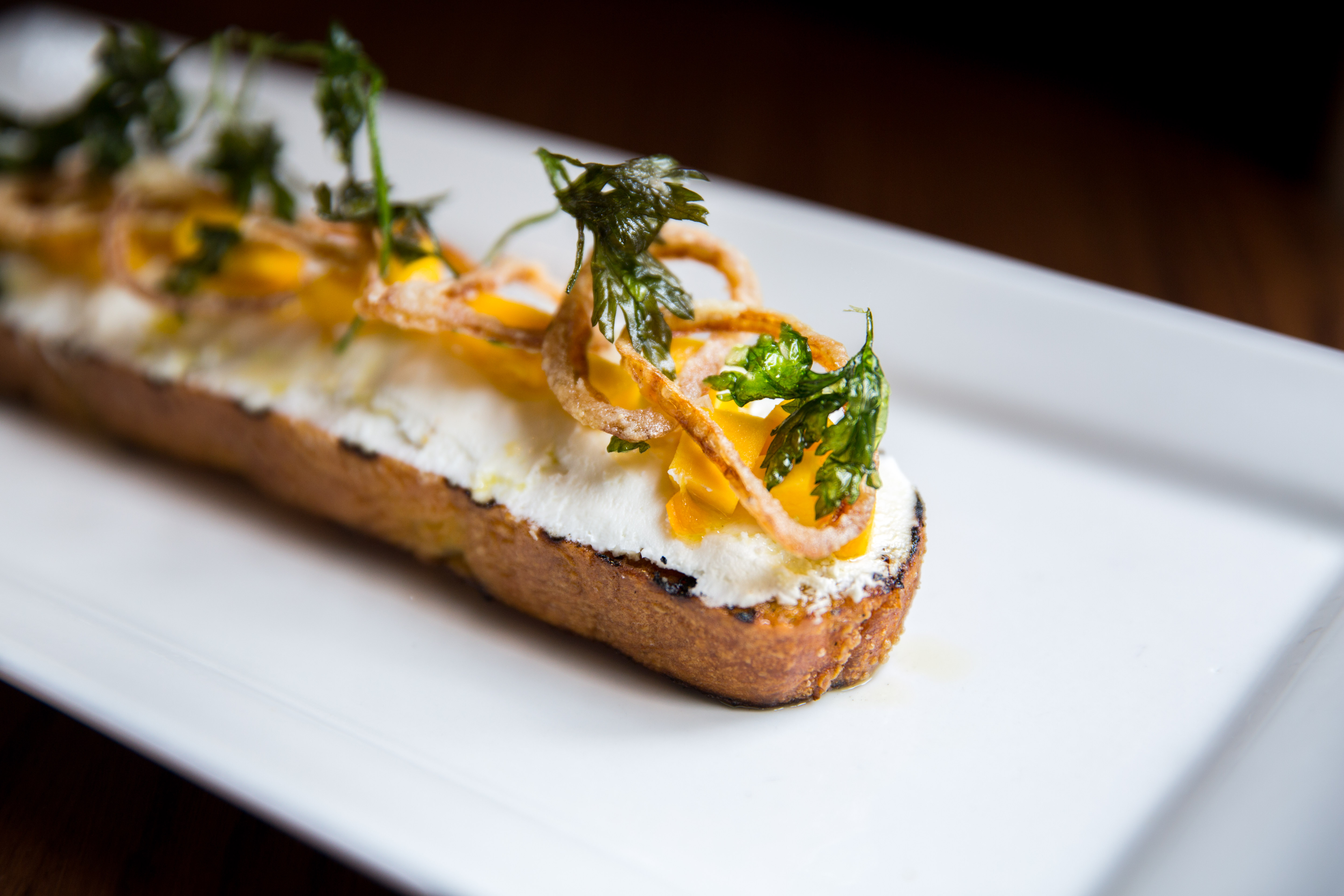<p>Pumpkin Bruschetta, grilled ciabatta goat cheese, sweet & sour pumpkin fried shallots, parsley.{&nbsp;} You can find these amazing pumpkin items at Tulio until October 31! (Image: Adela Lee).</p>
