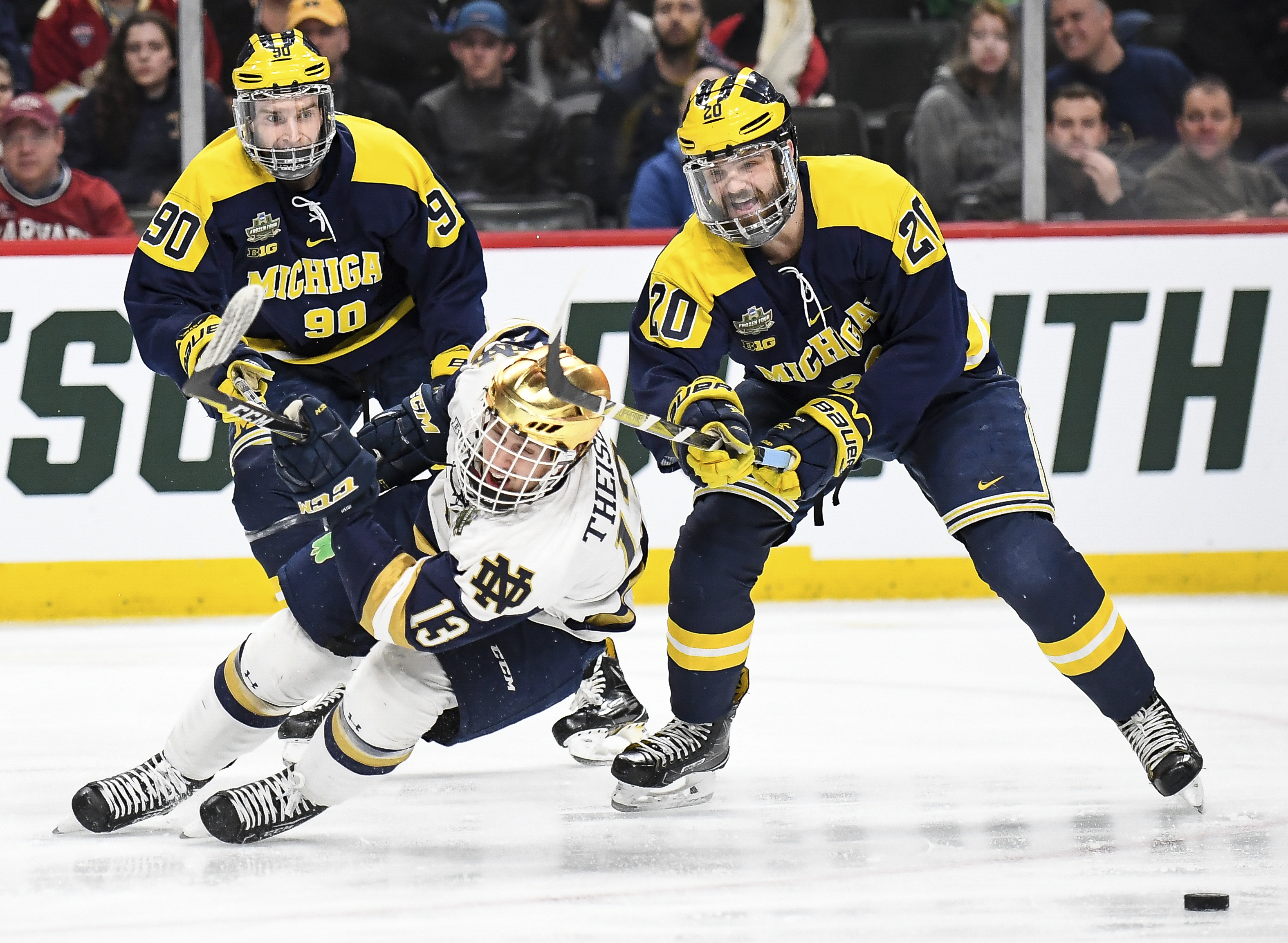 Michigan forward Cooper Marody (20) takes the skates out from under Notre Dame forward Colin Theisen (13), and is called for hooking during the first period of a semifinal in the NCAA men's Frozen Four hockey tournament Thursday, April 5, 2018, in St. Paul, Minn. (Aaron Lavinsky/Star Tribune via AP)