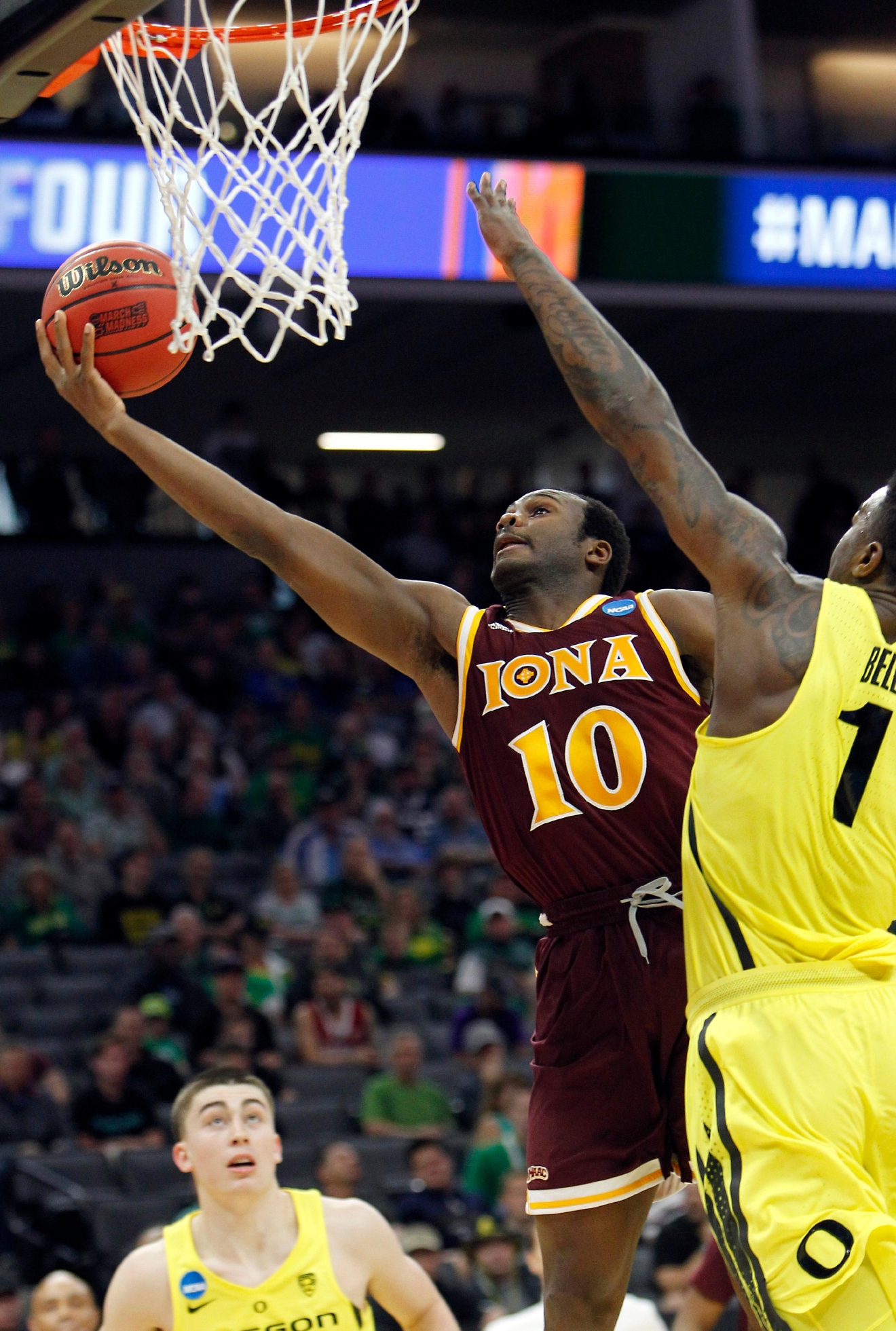 Iona guard Jon Severe, left, goes to the basket against Oregon forward Jordan Bell, right, during the first half of a first-round game in the men's NCAA college basketball tournament in Sacramento, Calif., Friday, March 17, 2017. (AP Photo/Steve Yeater)