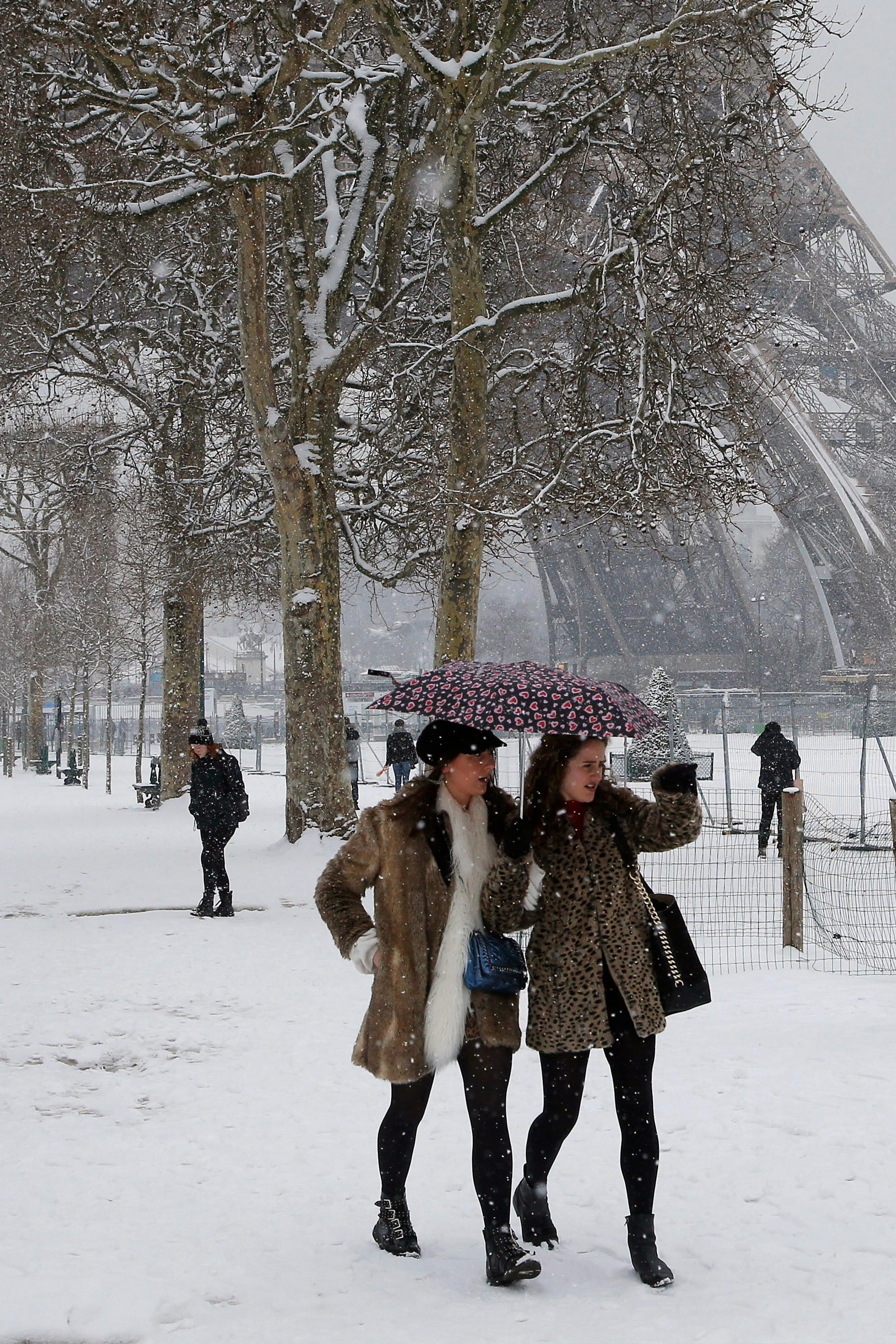 People stroll on the snow-covered Champ de Mars during a snowfall in Paris, France, Friday, Feb. 9, 2018. The Eiffel Tower is closed and authorities are telling drivers in the Paris region to stay home as snow and freezing rain have hit a swath of France ill-prepared for the wintry weather. (AP Photo/Michel Euler)