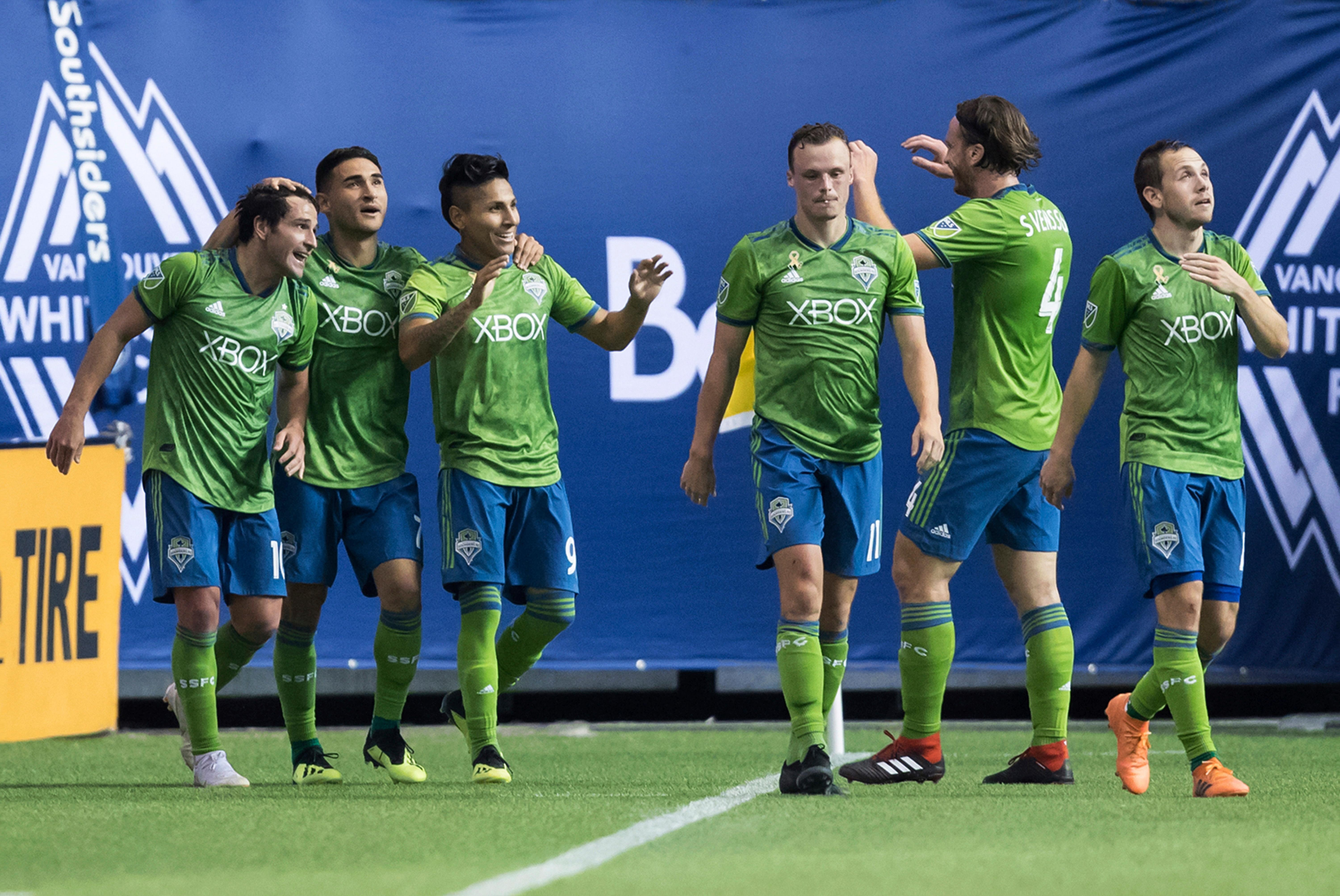 Seattle Sounders' Nicolas Lodeiro, from left to right, Cristian Roldan, Raul Ruidiaz, Brad Smith, Gustav Svensson and Harry Shipp celebrate Ruidiaz's second goal against the Vancouver Whitecaps during the first half of an MLS soccer match, Saturday, Sept. 15, 2018, in Vancouver, British Columbia. (Darryl Dyck/The Canadian Press via AP)