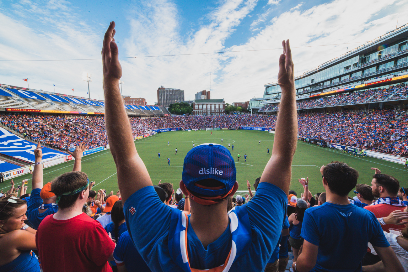 "Pictured: An FC Cincinnati fan raises his arms in celebration from the gallery ""Every Cincinnatian Should Experience At Least One FC Cincinnati Match"" / Image: Louis Rideout // Published: 12.31.17<p></p>"